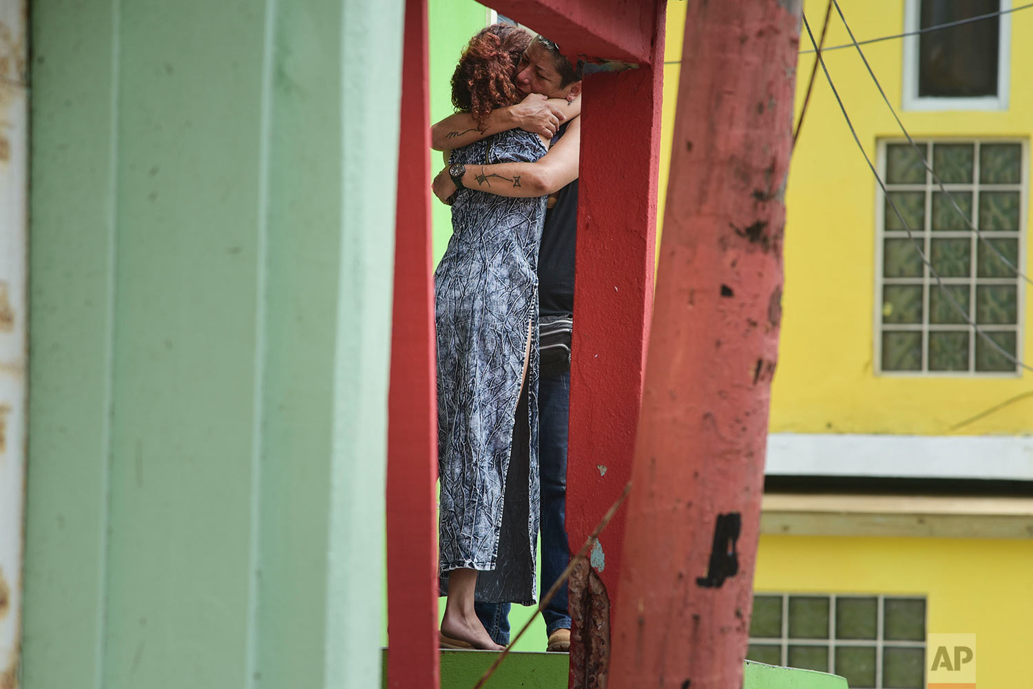 Residents at La Perla community in Old San Juan comfort one another as the community recovers from Hurricane Maria, in San Juan, Puerto Rico, Monday, Sept. 25, 2017. (AP Photo/Carlos Giusti)