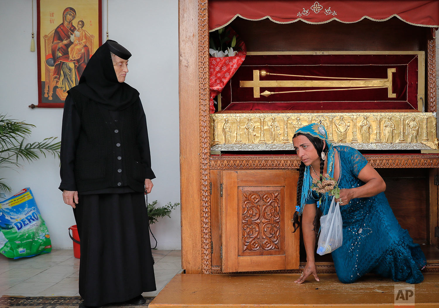 In this Friday, Sept. 8, 2017, photograph, an orthodox nun watches a Roma woman passing under a gold plated coffin containing holy remains at the Bistrita monastery in Costesti, Romania. (AP Photo/Vadim Ghirda)