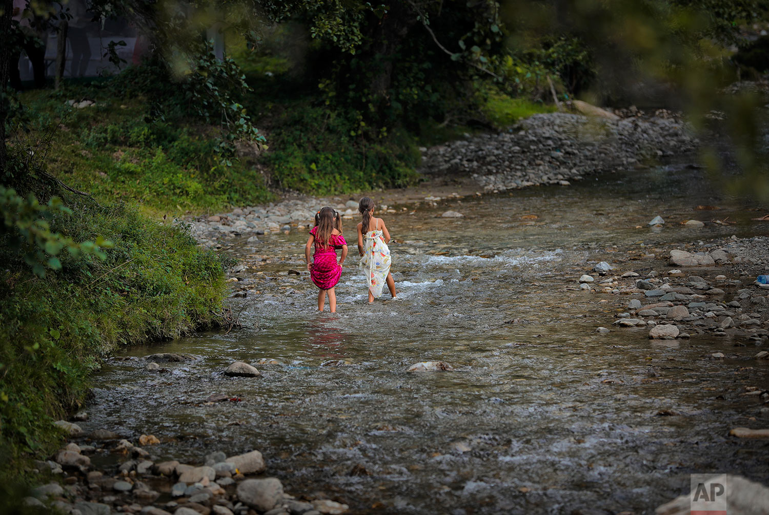 In this Friday, Sept. 8, 2017 photograph, Roma girls walk in a river in Costesti, Romania. (AP Photo/Vadim Ghirda)