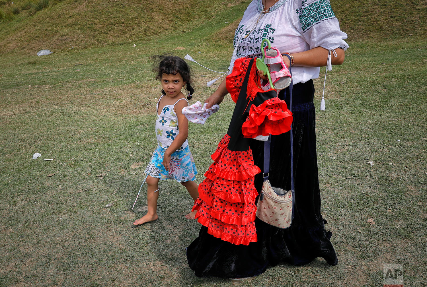 In this Friday, Sept. 8, 2017, photograph, a Roma girl walks next to a woman holding a party dress she bought for her in Costesti, Romania. (AP Photo/Vadim Ghirda)
