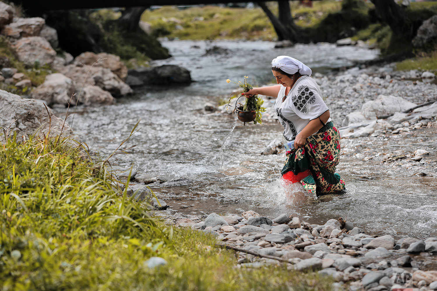 In this Friday, Sept. 8, 2017 photograph, Monica the Roma witch crosses a river pouring water from a container during what she described as a ritual to help unmarried women find good husbands in Costesti, Romania. (AP Photo/Vadim Ghirda)