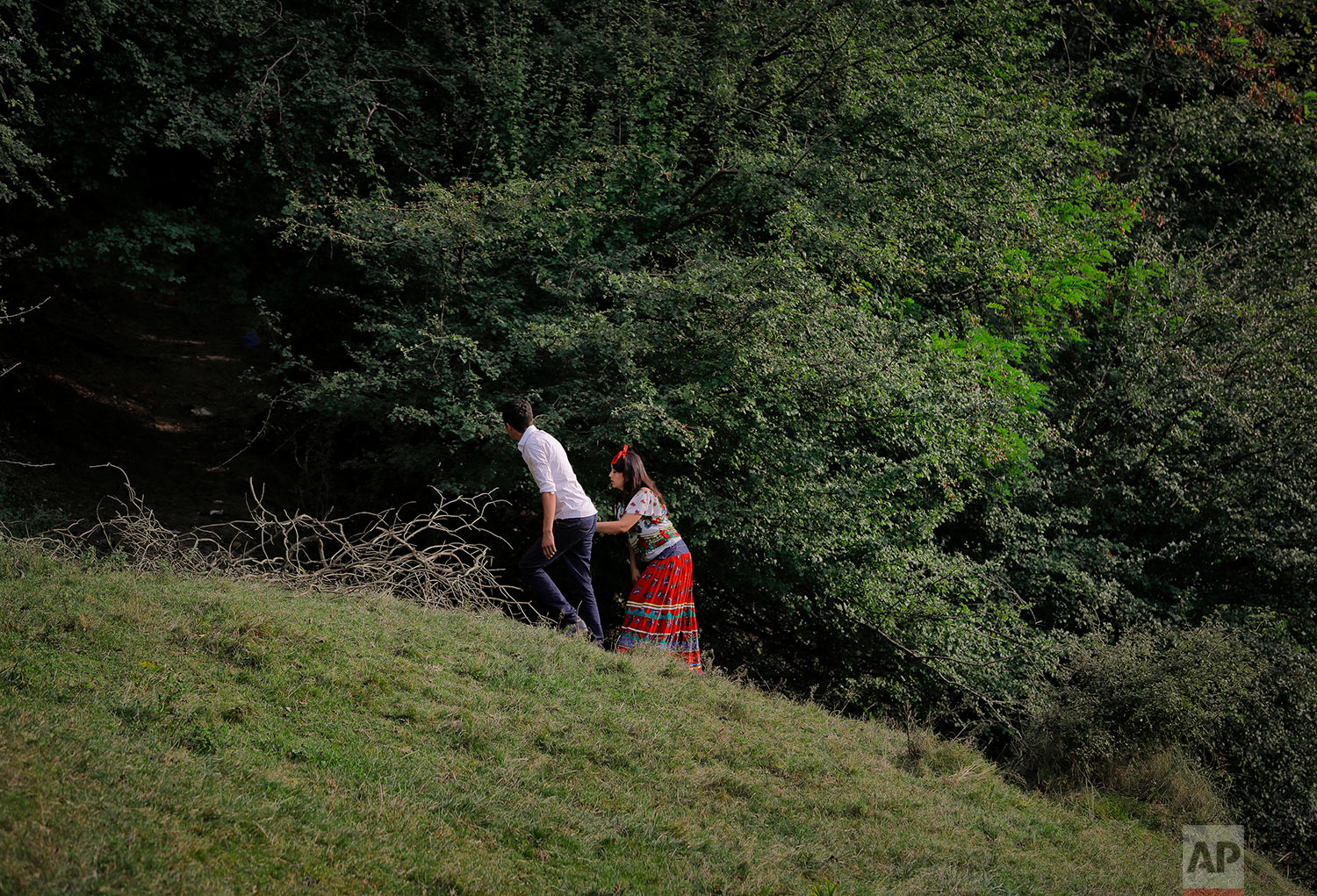 In this Friday, Sept. 8, 2017, photograph, a Roma couple walks on a hillside in Costesti, Romania. (AP Photo/Vadim Ghirda)