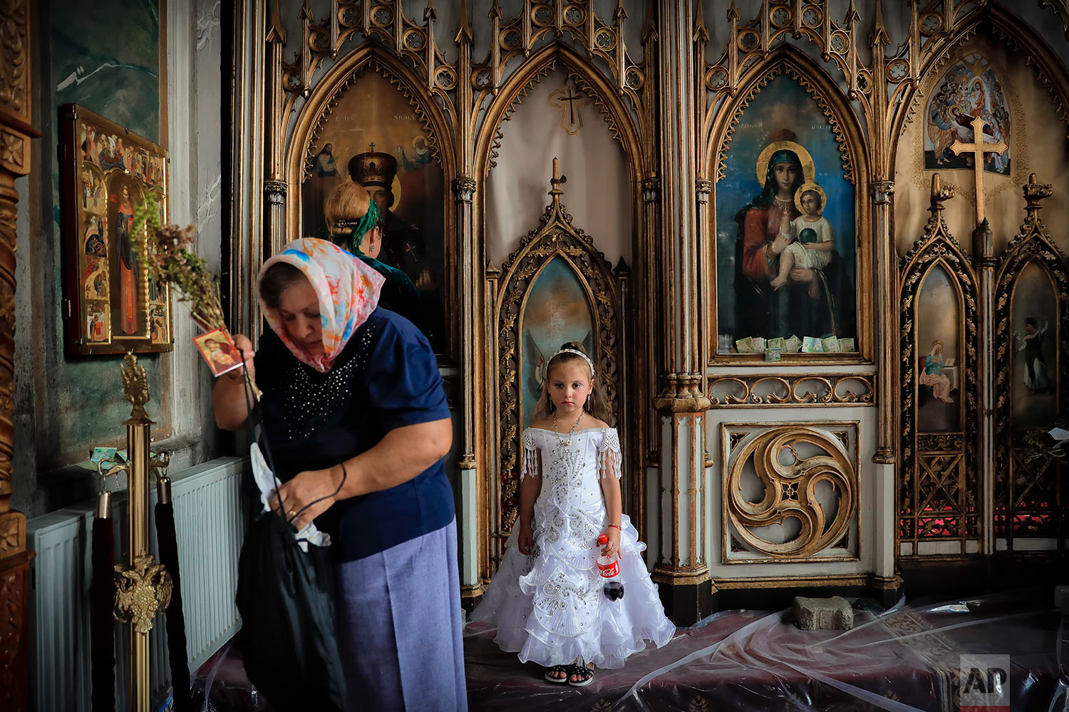 In this Friday, Sept. 8, 2017 photograph, a Roma girl waits for her mother after walking by the altar of the church in the Bistrita monastery compound in Costesti, Romania. (AP Photo/Vadim Ghirda)
