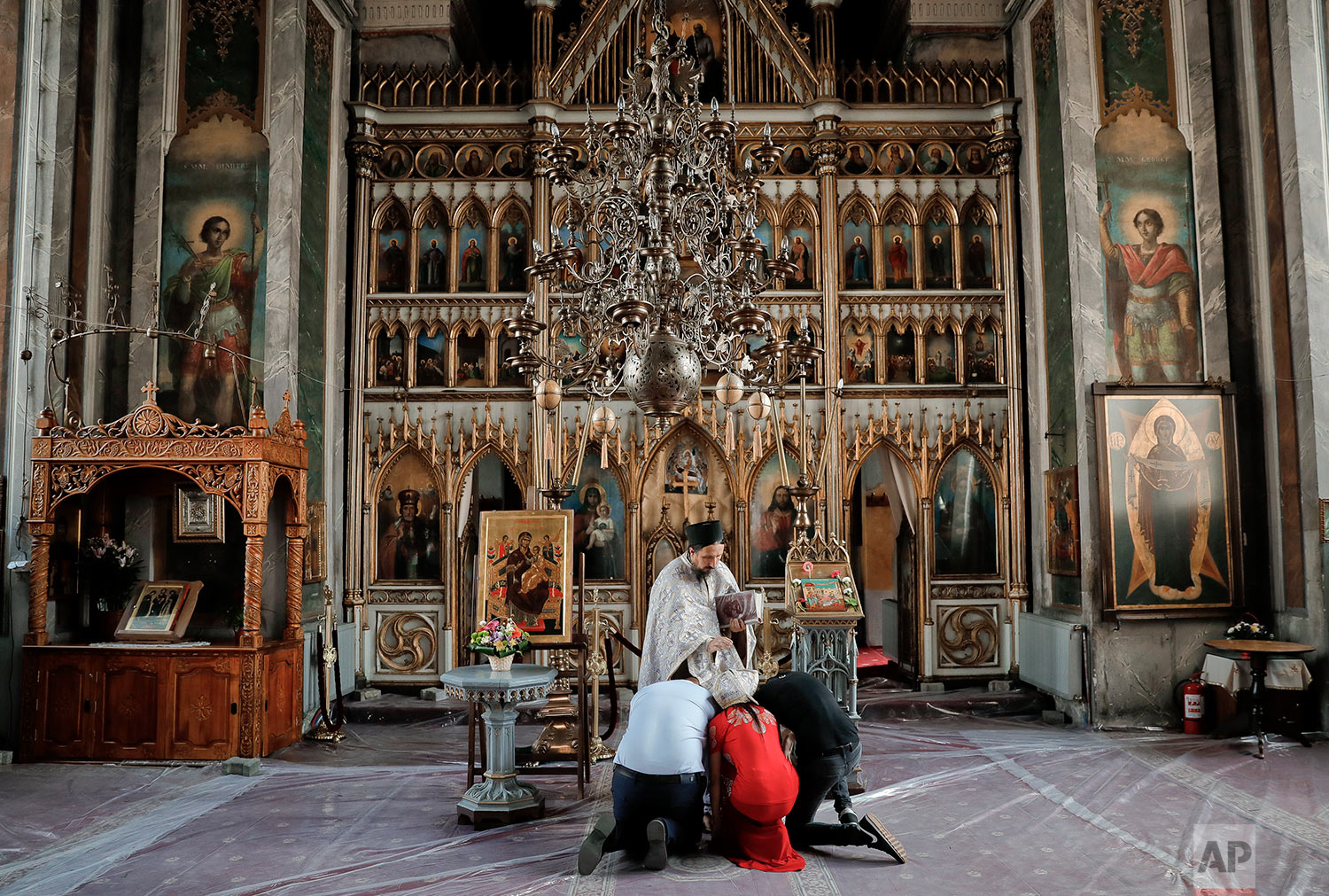 In this Friday, Sept. 8, 2017 photograph, members of the Roma community kneel before a priest reading prayers at the church in the Bistrita monastery compound in Costesti, Romania. (AP Photo/Vadim Ghirda)
