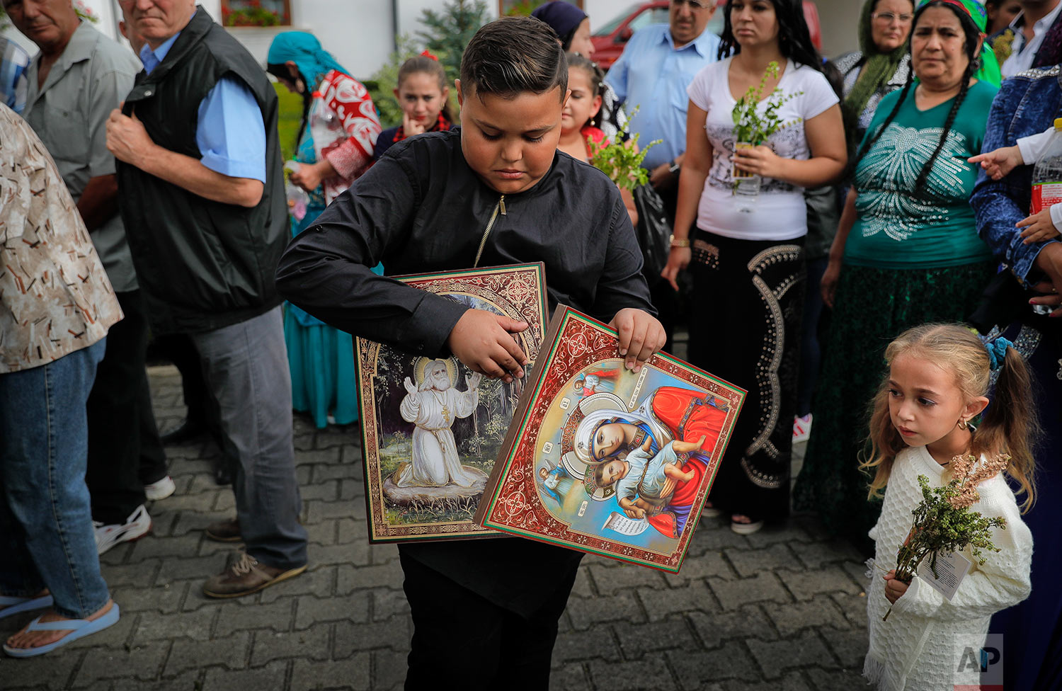 In this Friday, Sept. 8, 2017 photograph, a Roma handles icons as others wait in line to touch the holy remains of a saint at the Bistrita monastery compound in Costesti, Romania.  (AP Photo/Vadim Ghirda)