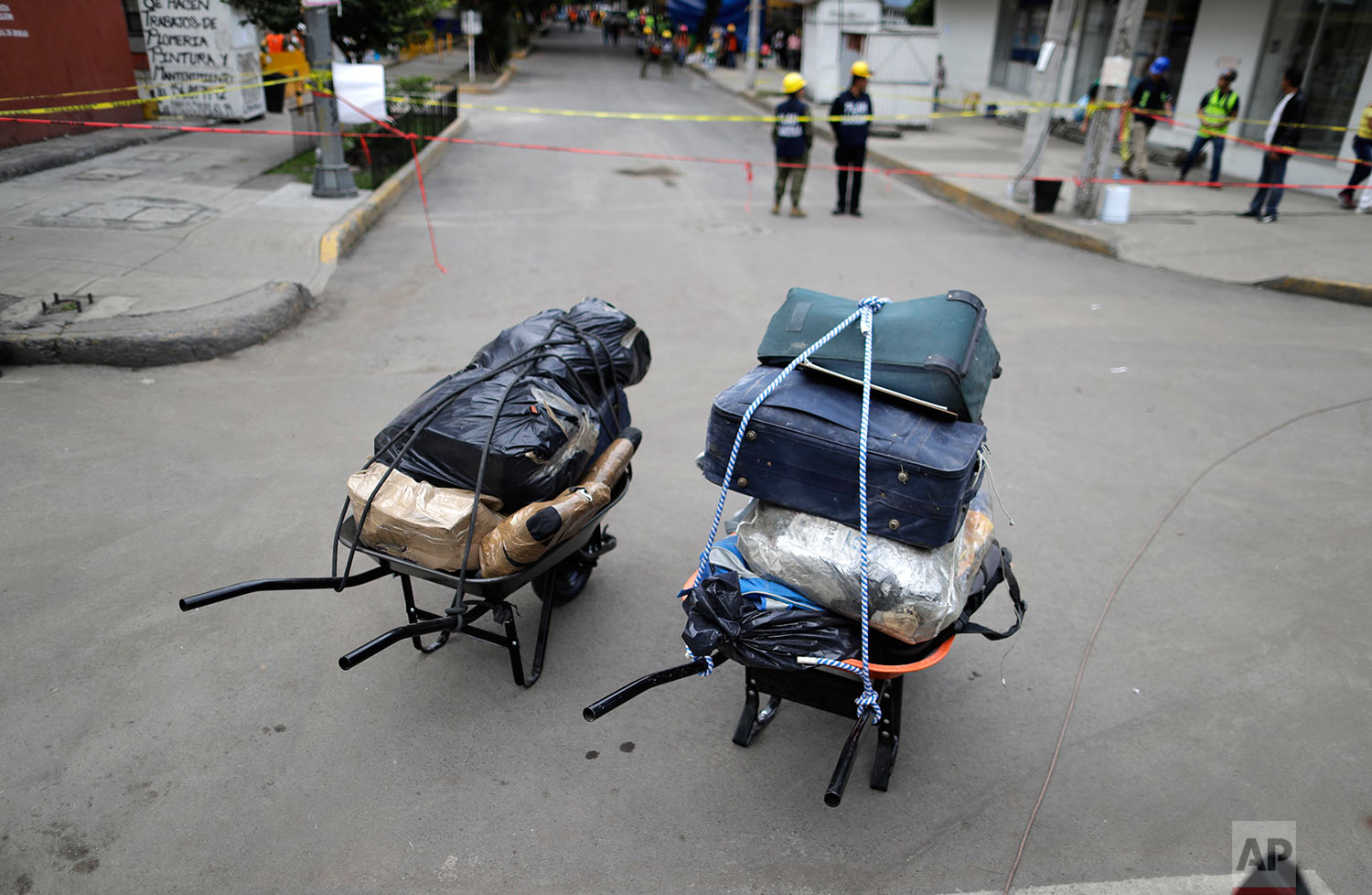 Wheelbarrows hold luggage of some of the residents who had to evacuate their apartment complex in the southern neighborhood of Tlalpan in Mexico City, Monday, Sept. 25, 2017.  (AP Photo/Natacha Pisarenko)