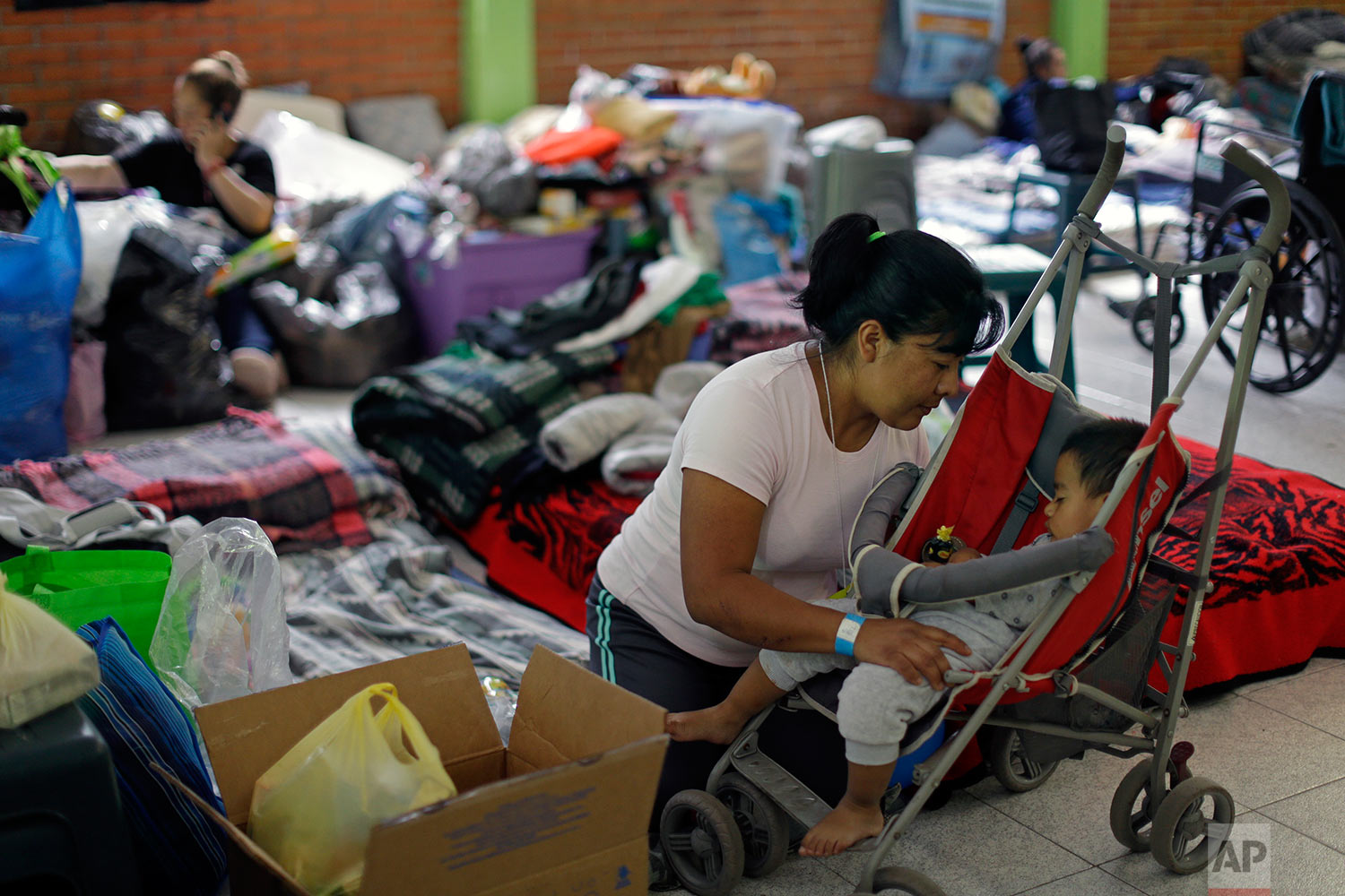 Florencia Cortes, 37, cares for her son Jonatan at the Francisco Kino school, which was turned into a temporary shelter for residents evacuated from the large apartment complex in the Tlalpan neighborhood of Mexico City, Monday, Sept. 25, 2017. Cortes was pulled from the rubble of her apartment building along with her one-year, eight-months-old son, Jonatan. In order to get her son out, she had to swing him toward the building's plumber, who happened to be outside. He caught ahold of the boy by his foot. (AP Photo/Natacha Pisarenko)
