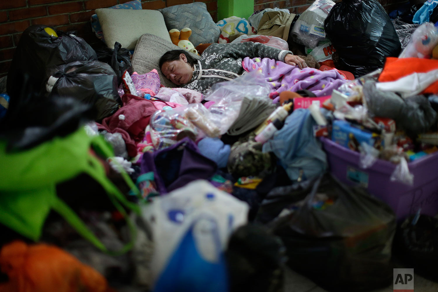 A woman sleeps at the Francisco Kino school, which was turned into a temporary shelter for residents evacuated from the large apartment complex, in the Tlalpan neighborhood of Mexico City, Monday, Sept. 25, 2017.  (AP Photo/Natacha Pisarenko)
