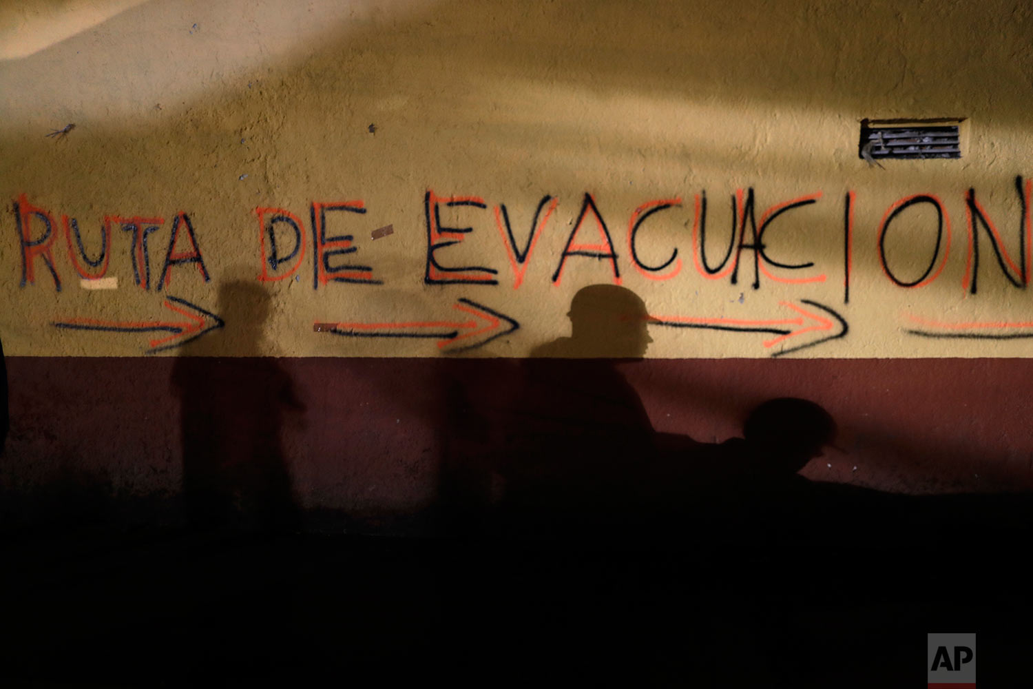"""Shadows of rescue workers and volunteers are cast on the wall of an apartment building covered with the spray painted words in Spanish: """"Evacuation route"""" in the southern neighborhood of Tlalpan in Mexico City, Monday, Sept. 25, 2017. (AP Photo/Natacha Pisarenko)"""