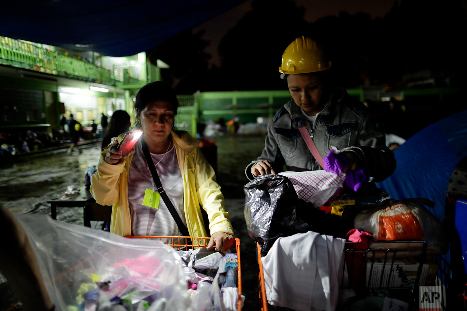 Volunteers sort donated clothes at the Francisco Kino school, which was turned into a temporary shelter for residents evacuated from the large apartment complex in the Tlalpan neighborhood of Mexico City, Monday, Sept. 25, 2017. (AP Photo/Natacha Pisarenko)