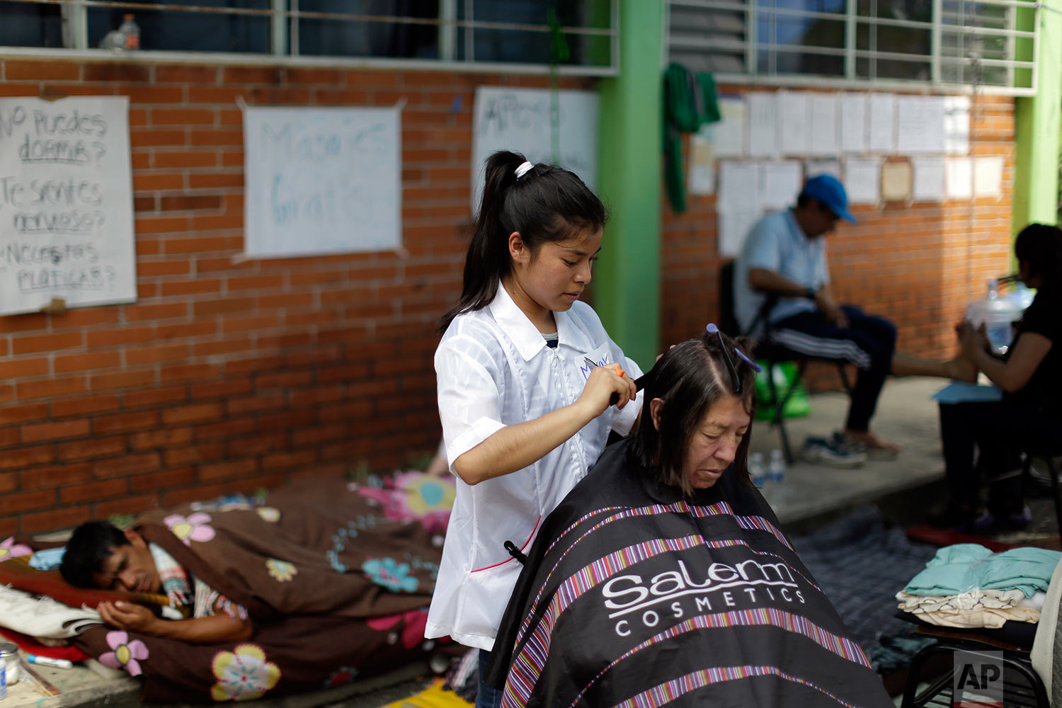 Lidia Benhunmea has her hair done at at the Francisco Kino school, which was turned into a temporary shelter for residents evacuated from the large apartment complex in the Tlalpan neighborhood of Mexico City, Monday, Sept. 25, 2017.   (AP Photo/Natacha Pisarenko)