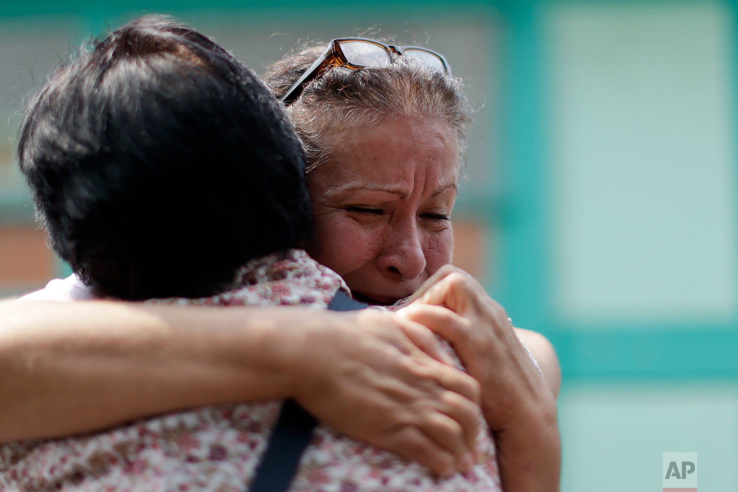 Maria Susana Fernandez Lopez embraces a neighbor outside the Francisco Kino school, which was turned into a temporary shelter for residents evacuated from a large apartment complex in the Tlalpan neighborhood of Mexico City, Monday, Sept. 25, 2017. (AP Photo/Natacha Pisarenko)