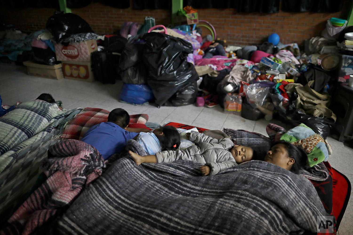 Florencia Cortes, 37, right, sleeps next to her son Jonatan at the Francisco Kino school, which was turned into a temporary shelter for residents evacuated from the large apartment complex in the Tlalpan neighborhood of Mexico City, Monday, Sept. 25, 2017. Cortes was pulled from the rubble of her apartment building along with her one-year, eight-months-old son, Jonatan. In order to get her son out, she had to swing him toward the building's plumber, who happened to be outside. He caught ahold of the boy by his foot. (AP Photo/Natacha Pisarenko)