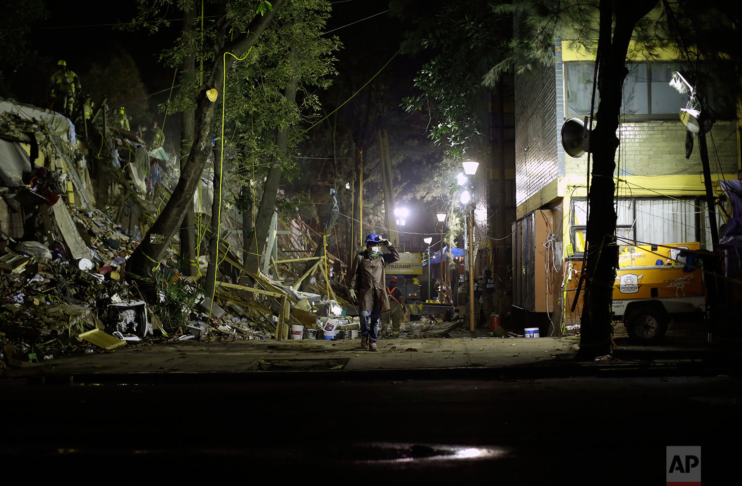 A rescue worker walks between a collapsed apartment building and another that remained standing at a large apartment complex in the Tlalpan neighborhood of Mexico City, Monday, Sept. 25, 2017.  (AP Photo/Natacha Pisarenko)