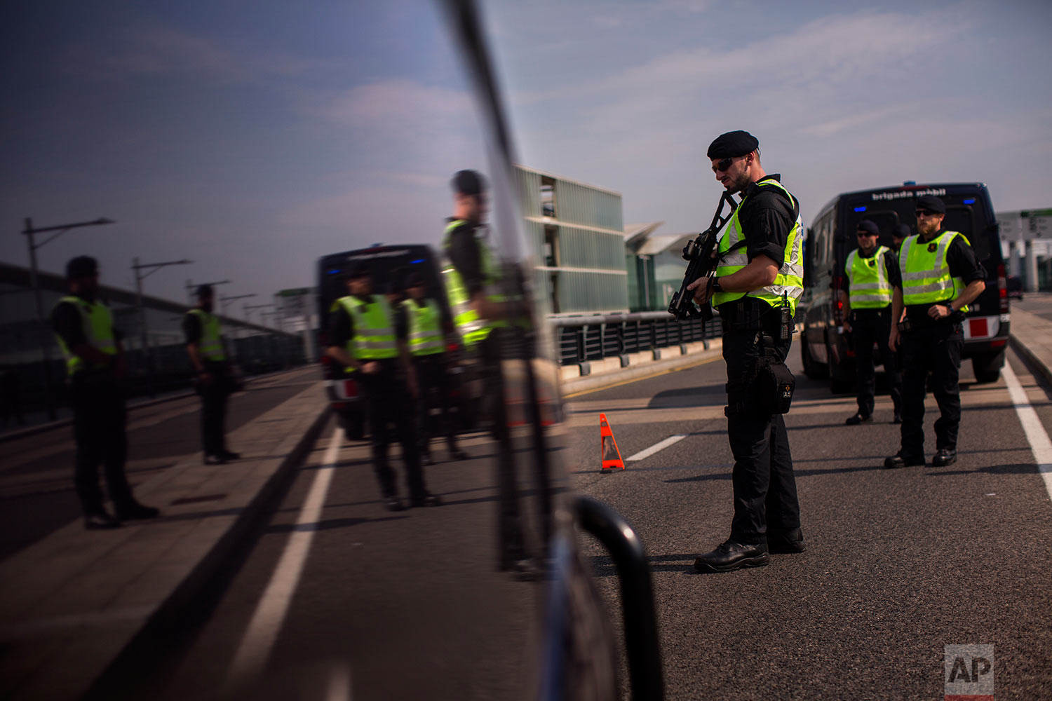 In this Saturday, Sept. 23, 2017 photo, police officers of Catalan Mossos d'Esquadra stand guard on a checkpoint near the airport in Barcelona, Spain. (AP Photo/Emilio Morenatti)
