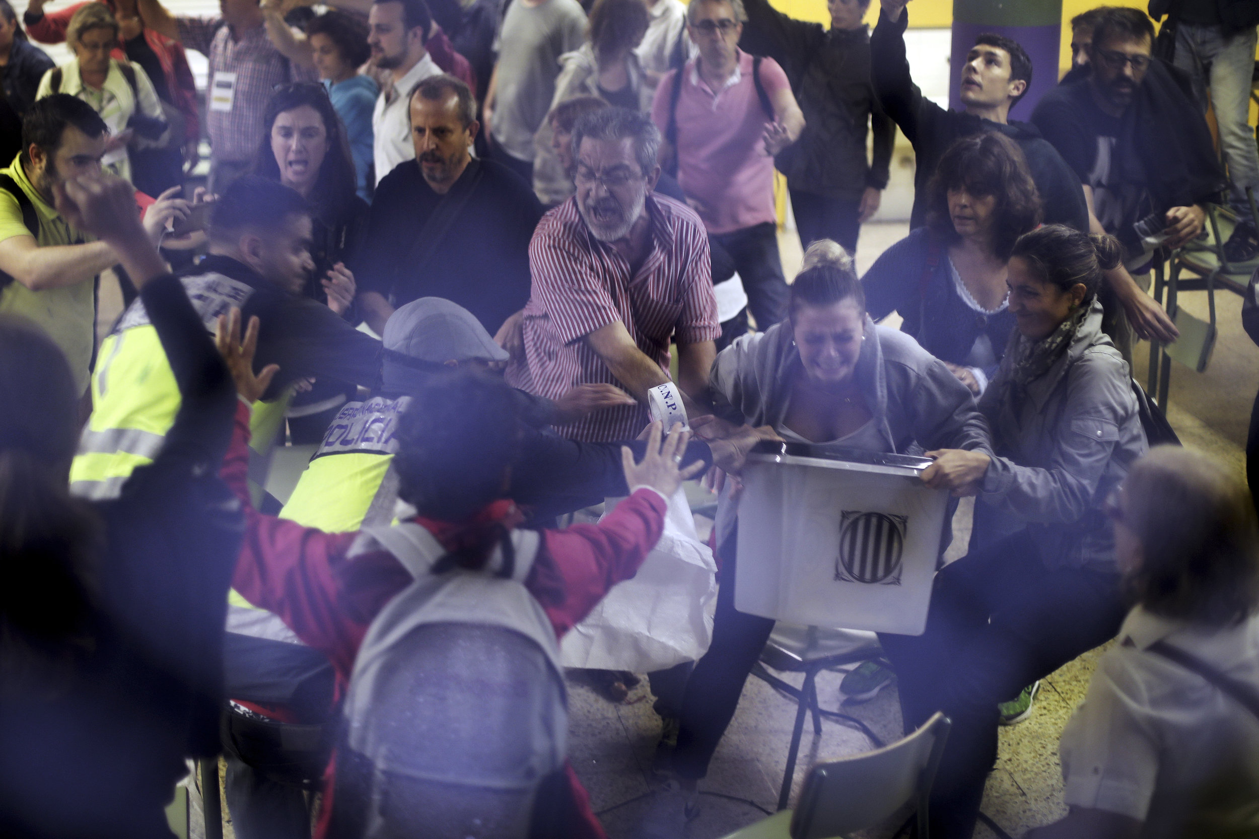 Spanish National Police officers in plain clothes try to snatch a ballot box from polling station officials at the Ramon Llull school assigned to be a polling station by the Catalan government in Barcelona, Spain, early Sunday, Oct. 1, 2017. (AP Photo/Manu Brabo)