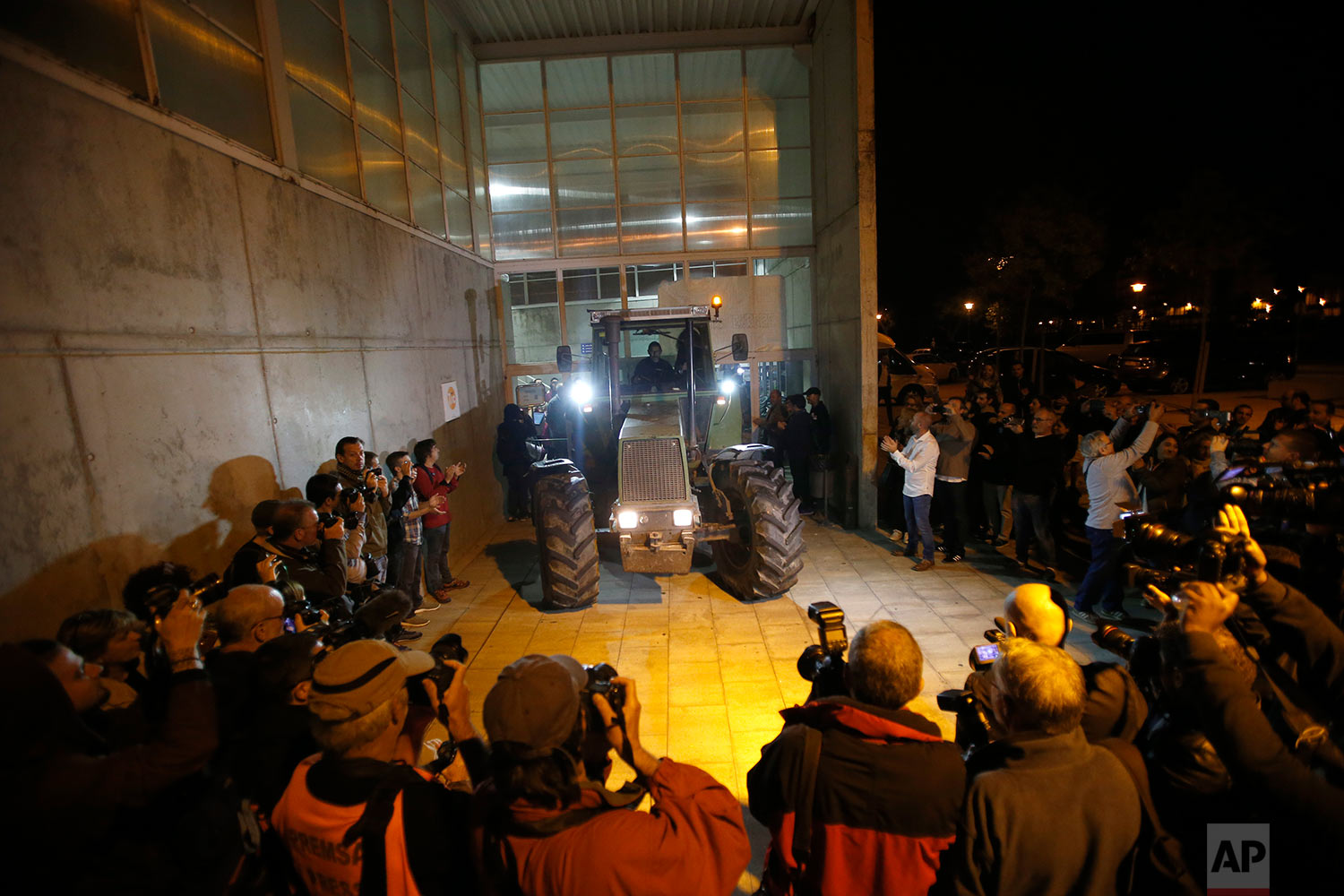 As journalists take pictures, a parked tractor blocks the door of a sports center, assigned to be a polling station by the Catalan government and where Catalan President Carles Puigdemont is expected to vote, in Sant Julia de Ramis, near Girona, Spain, Sunday, Oct. 1, 2017. Catalan pro-referendum supporters vowed to ignore a police ultimatum to leave the schools they are occupying to use in a vote seeking independence from Spain. (AP Photo/Francisco Seco)