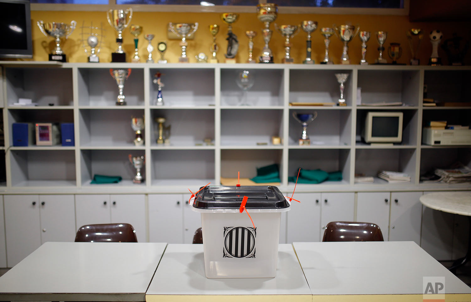 A ballot box sits on a table at a sports center assigned to be a polling station by the Catalan government and where Catalan President Carles Puigdemont is expected to vote, in Sant Julia de Ramis, near Girona, Spain, Sunday, Oct. 1, 2017. Catalan pro-referendum supporters vowed to ignore a police ultimatum to leave the schools they are occupying to use in a vote seeking independence from Spain. (AP Photo/Francisco Seco)