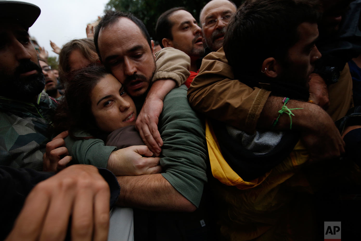 Pro-referendum supporters embrace each other as Spanish National Police tries to remove them from the Ramon Llull school assigned to be a polling station by the Catalan government in Barcelona, Spain, early Sunday, 1 Oct. 2017. Catalan pro-referendum supporters vowed to ignore a police ultimatum to leave the schools they are occupying to use in a vote seeking independence from Spain. (AP Photo/Emilio Morenatti)