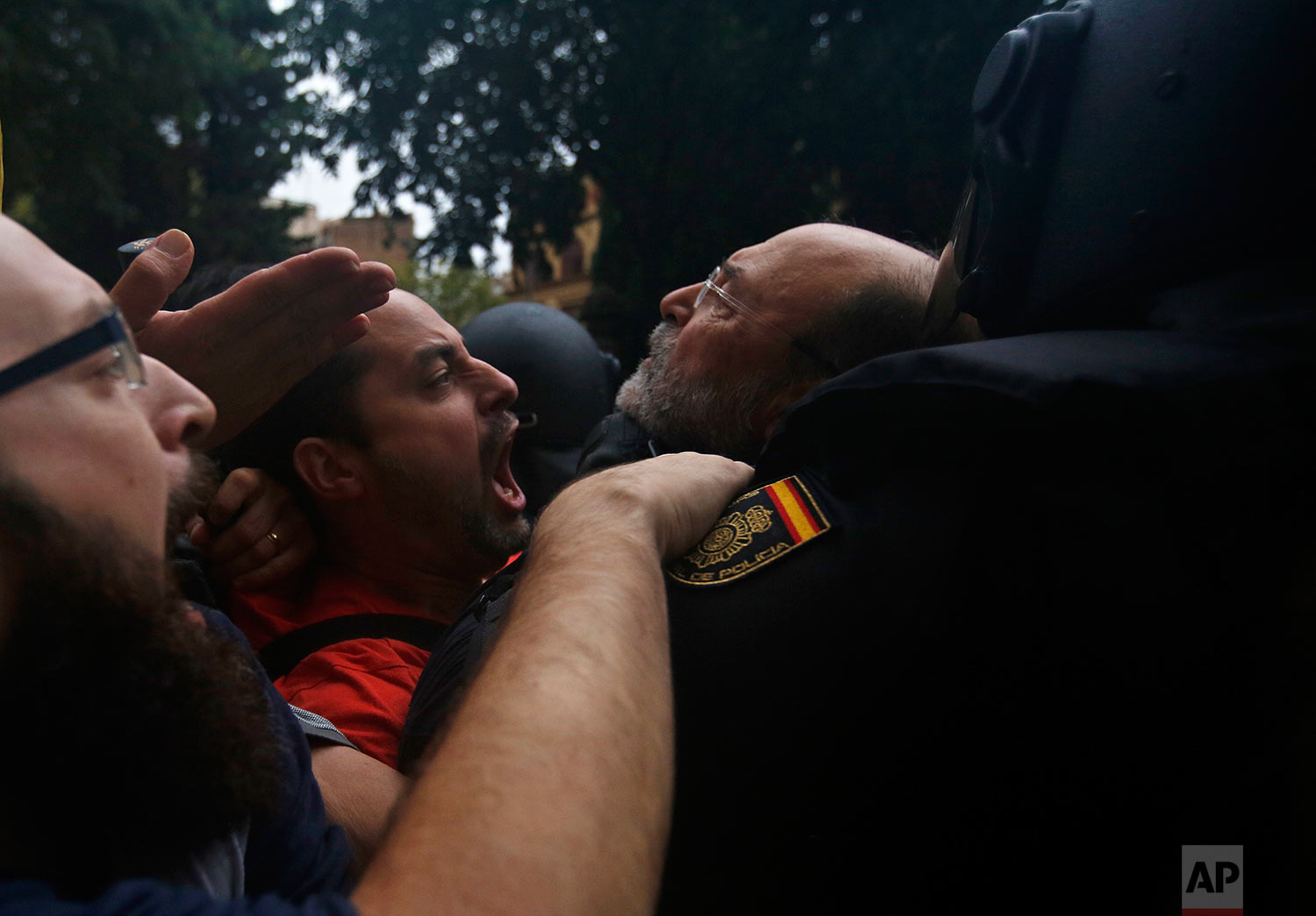 Spanish National Police pushes away Pro-referendum supporters outside the Ramon Llull school assigned to be a polling station by the Catalan government in Barcelona, Spain, early Sunday, Oct. 1, 2017. Catalan pro-referendum supporters vowed to ignore a police ultimatum to leave the schools they are occupying to use in a vote seeking independence from Spain. (AP Photo/Emilio Morenatti)