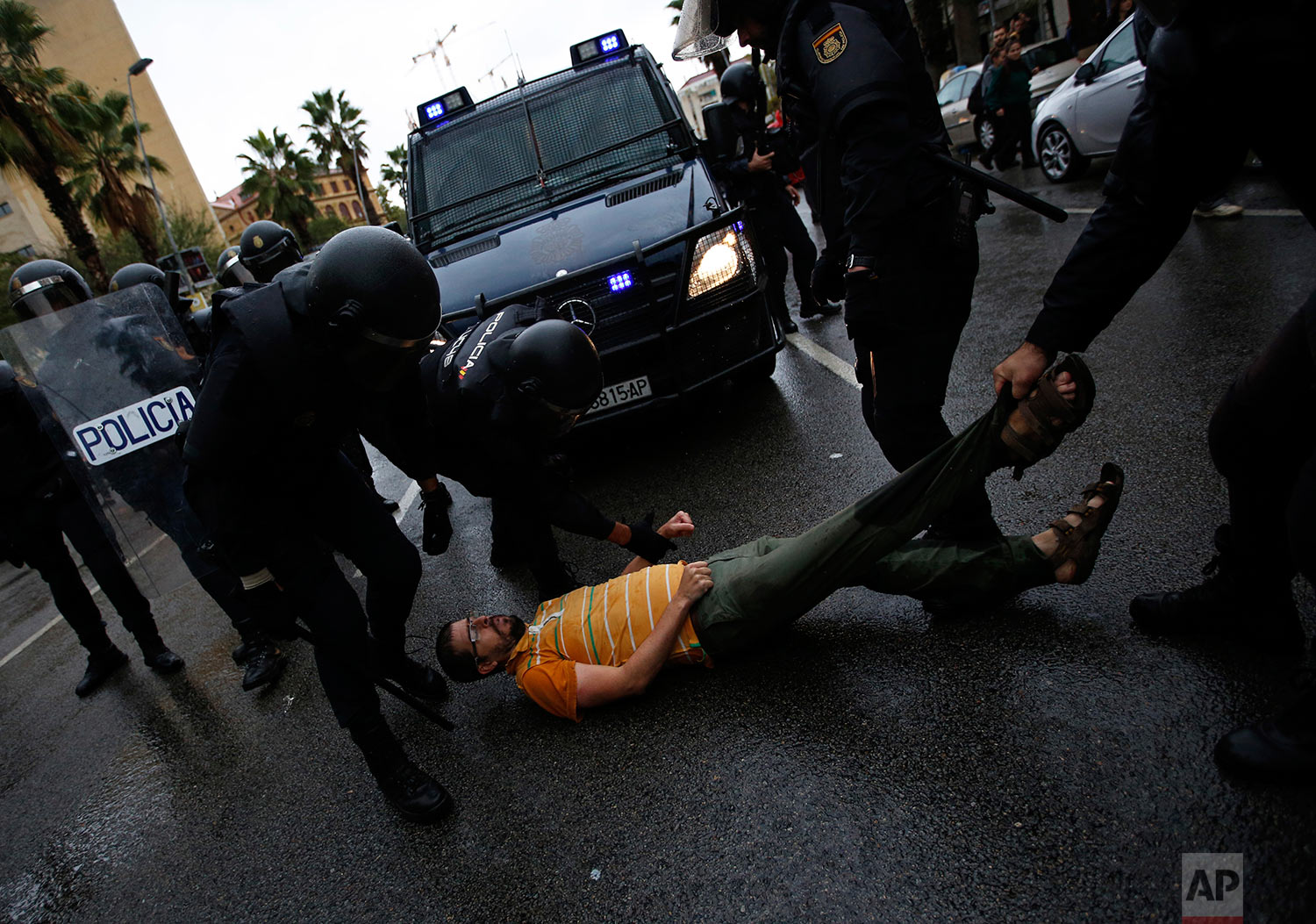 Spanish National Police officers drags a man trying to block a police van outside the Ramon Llull school assigned to be a polling station by the Catalan government in Barcelona, Spain, early Sunday, Oct. 1, 2017. Catalan pro-referendum supporters vowed to ignore a police ultimatum to leave the schools they are occupying to use in a vote seeking independence from Spain. (AP Photo/Emilio Morenatti)