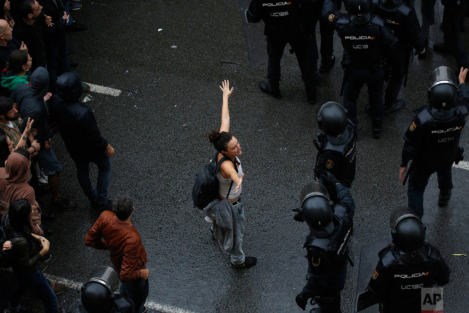 A woman holds her hands up next Spanish National Police as they try to block voters from reaching a voting site at a school assigned to be a polling station by the Catalan government in Barcelona, Spain, Sunday, Oct. 1, 2017. Catalan pro-referendum supporters vowed Saturday to ignore a police ultimatum to leave the schools they are occupying to use in a vote seeking independence from Spain. (AP Photo/Emilio Morenatti)