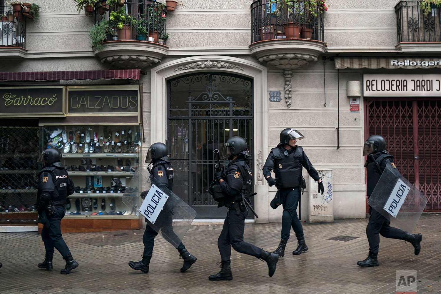 Spanish riot police takes position near a voting site at a school assigned to be a polling station by the Catalan government in Barcelona, Spain, Sunday, Oct. 1, 2017. Spanish riot police have forcefully removed and clashed with would-be voters in several polling stations in Barcelona.(AP Photo/Felipe Dana)