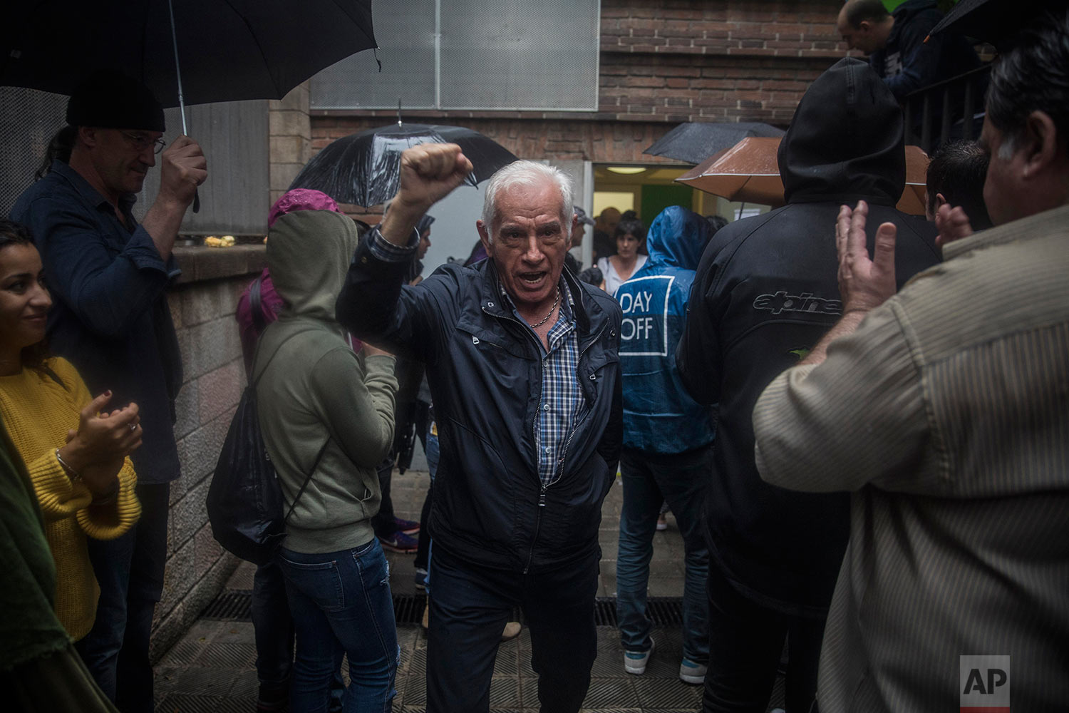 A man reacts after voting at a school listed to be a polling station by the Catalan government in Barcelona, Spain, Sunday, Oct. 1, 2017. Polling has begun in a banned referendum on Catalonia's independence, with the first voters casting ballots amid cheers in some of the designated polling stations. (AP Photo/Santi Palacios)