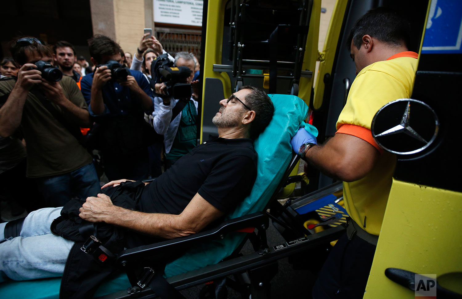 An injured man is taken into an ambulance near a school assigned to be a polling station by the Catalan government in Barcelona, Spain, Sunday, Oct. 1, 2017. Spanish riot police have forcefully removed a few hundred would-be voters from several polling stations in Barcelona.(AP Photo/Emilio Morenatti)