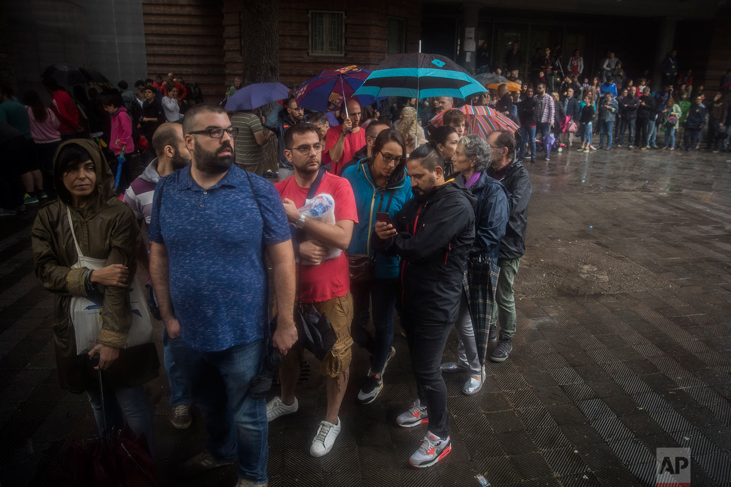 People queue to vote at a school listed to be a polling station by the Catalan government in Barcelona, Spain, Sunday, Oct. 1, 2017. Polling has begun in a banned referendum on Catalonia's independence, with the first voters casting ballots. Spanish riot police have smashed their way into polling stations to try to halt a disputed independence referendum and fired rubber bullets at protesters. (AP Photo/Santi Palacios)