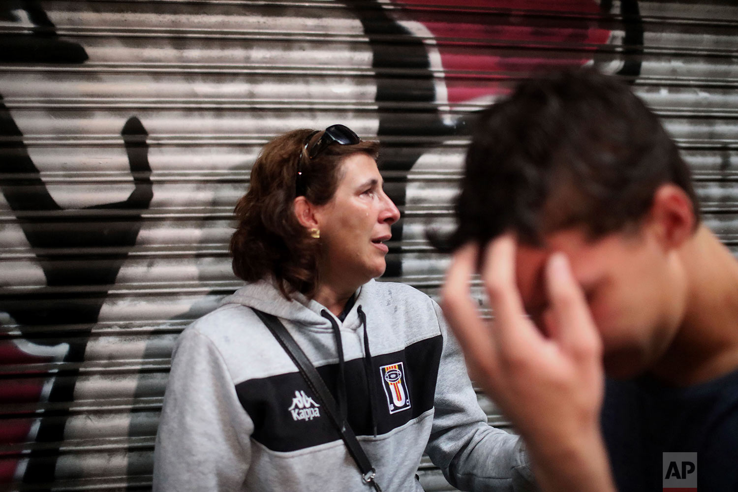 A woman and her son react as Spanish National Police storm the Ramon Llull school assigned to be a polling station by the Catalan government in Barcelona, Spain, early Sunday, 1 Oct. 2017. The Spanish government and its security forces are trying to prevent voting in the independence referendum, which is backed by Catalan regional authorities. Spanish officials had said force wouldn't be used, but that voting wouldn't be allowed. (AP Photo/Manu Brabo)