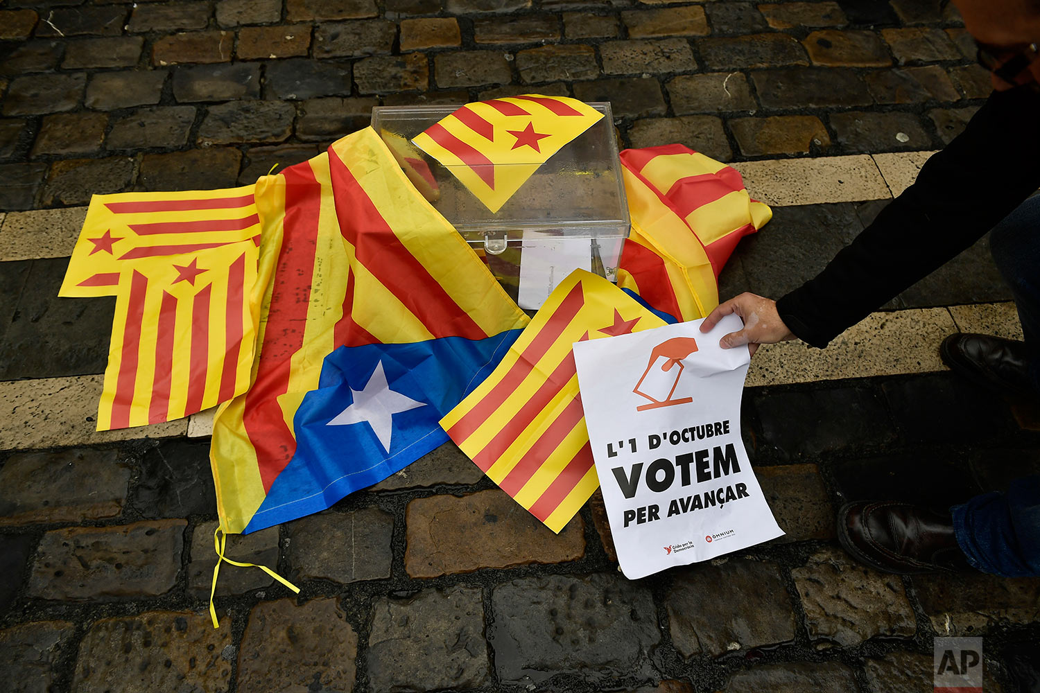 A pro independences supporter holds up a sign calling for the vote close to a mock ballot boxes covered with ''esteleda'' or Catalan pro independence flags in support of the Catalonia's secession referendum, in Pamplona, northern Spain, Sunday, Oct. 1, 2017.   Catalonia's regional government is holding a referendum Sunday on the possibility of breaking away from Spain, despite Spain's Constitutional Court ordering the vote to be suspended and prompting a police crackdown.  (AP Photo/Alvaro Barrientos)