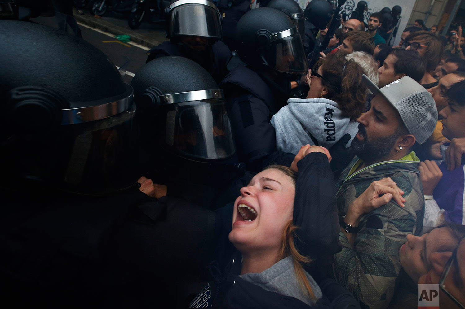 A girl grimaces as Spanish National Police pushes away Pro-referendum supporters outside the Ramon Llull school assigned to be a polling station by the Catalan government in Barcelona, Spain, early Sunday, 1 Oct. 2017. (AP Photo/Emilio Morenatti)