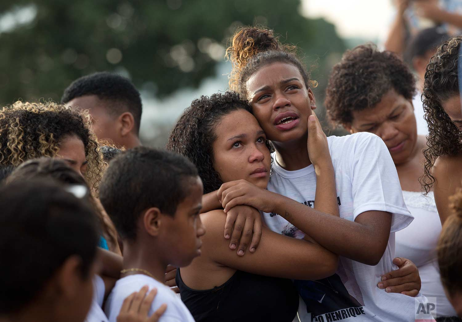 In this April 26, 2017 photo, relatives and friends attend the burial of 13-year-old Paulo Henrique Oliveira, in Rio de Janeiro, Brazil. The boy lived with his family in the Alemao complex of slums and was walking to visit a neighbor when he was mortally wounded by a stray bullet from a shootout between Brazilian police and drug traffickers. (AP Photo/Silvia Izquierdo)