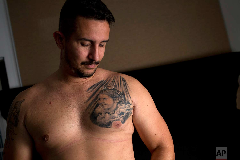 In this Aug. 17, 2017 photo, Felipe Fernandes poses shirtless to show the tattoo on his chest depicting his daughter Sofia Lara Braga, in Rio de Janeiro, Brazil. (AP Photo/Silvia Izquierdo)