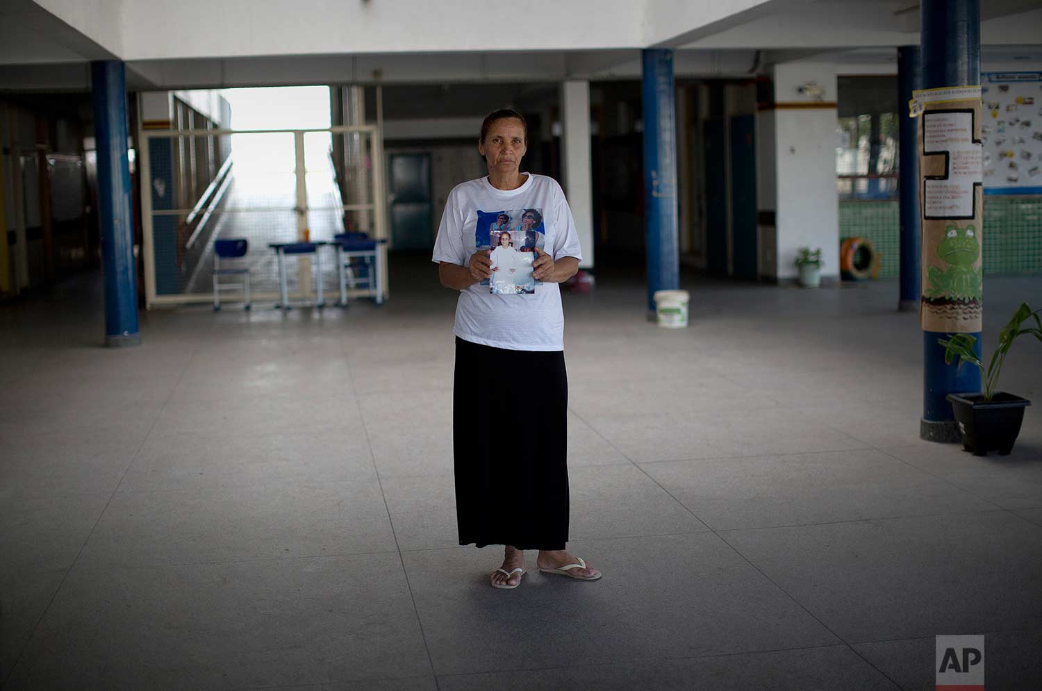 In this July 26, 2017 photo, Rosilene Alves Ferreira, mother of Maria Eduarda, stands in the exact spot where her daughter lay bleeding to death, inside the Daniel Piza Municipal School in the Acari slum, Rio de Janeiro, Brazil. Maria Eduarda was shot three times on March 30. The shots that killed the 13-year-old came from police targeting armed suspects near the school. (AP Photo/Silvia Izquierdo)