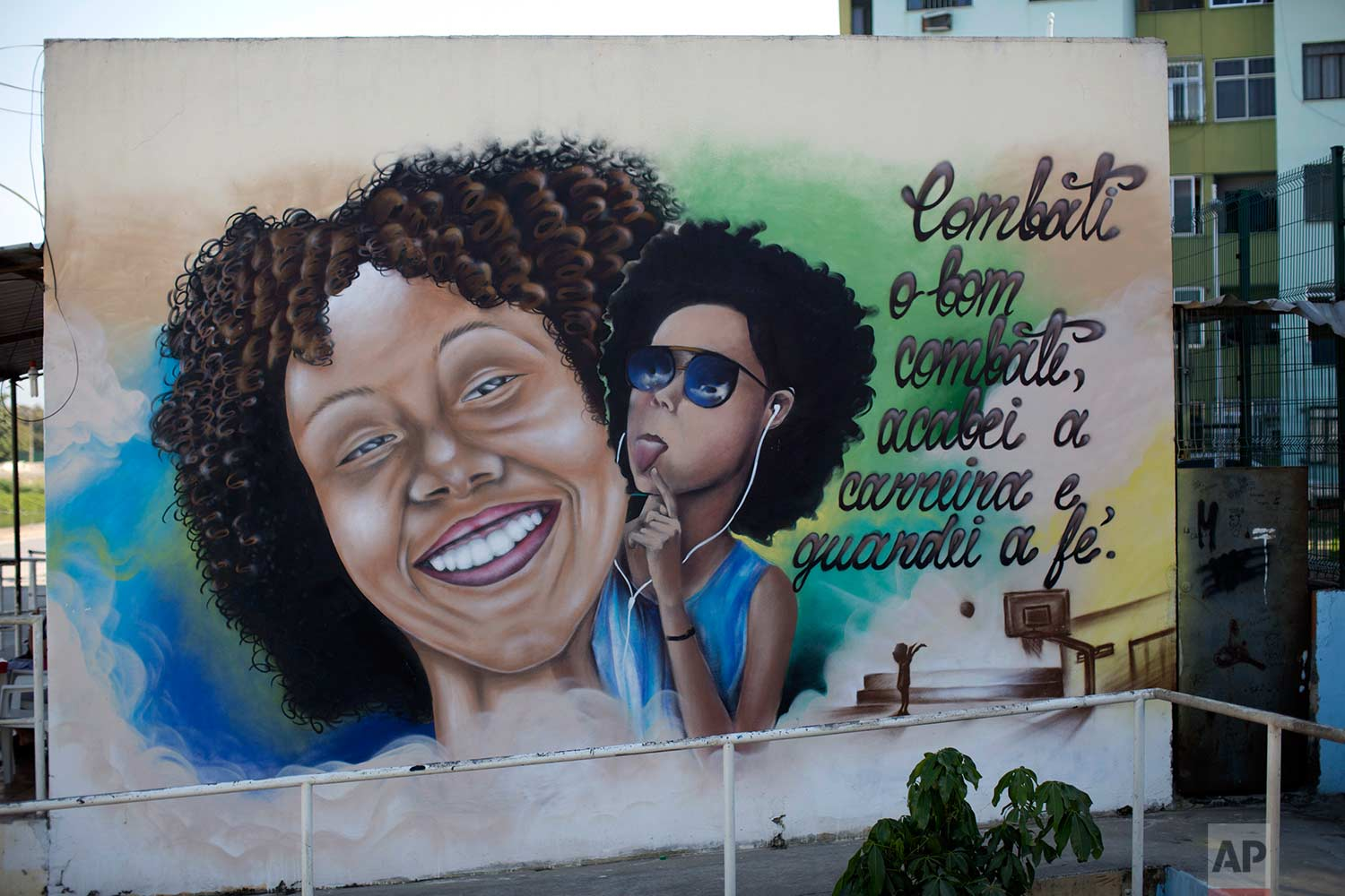 "This July 26, 2017 photo shows a mural with a message that reads in Portuguese; ""I fought the good fight, I ended the race and kept the faith"" alongside images of fellow student Maria Eduarda Alves da Conceicao, painted on a wall of the Daniel Piza Municipal School where she died when she was hit by three bullets not meant for her, in Rio de Janeiro, Brazil. The curly-haired teen dreamed of becoming a basketball player or an airline hostess. Instead she became a symbol of Rio's violence. (AP Photo/Silvia Izquierdo)"