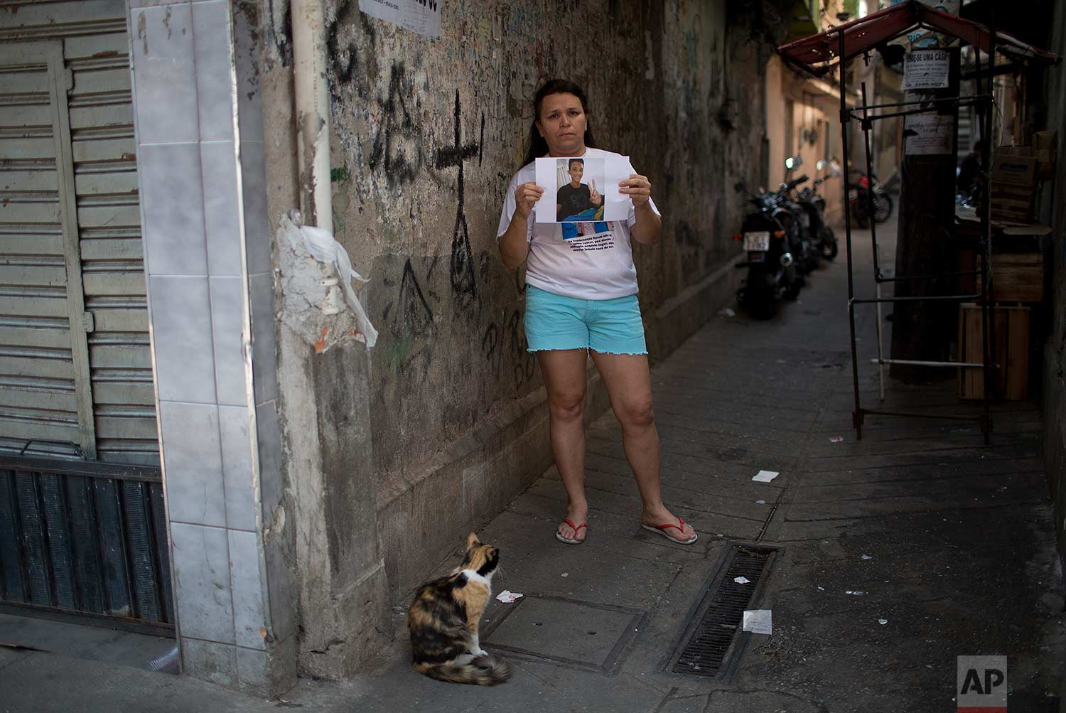 In this Aug. 13, 2017 photo, Tereza Farias poses with a photo of her 16-year-old son Felipe, on the exact spot where her son was also killed by gunfire not meant for him, in the Alemao complex of slums, in Rio de Janeiro, Brazil. Every night before going to bed, Farias looks at cellphone pictures taken by bystanders who witnessed her son's slender body lying in his own blood. (AP Photo/Silvia Izquierdo)