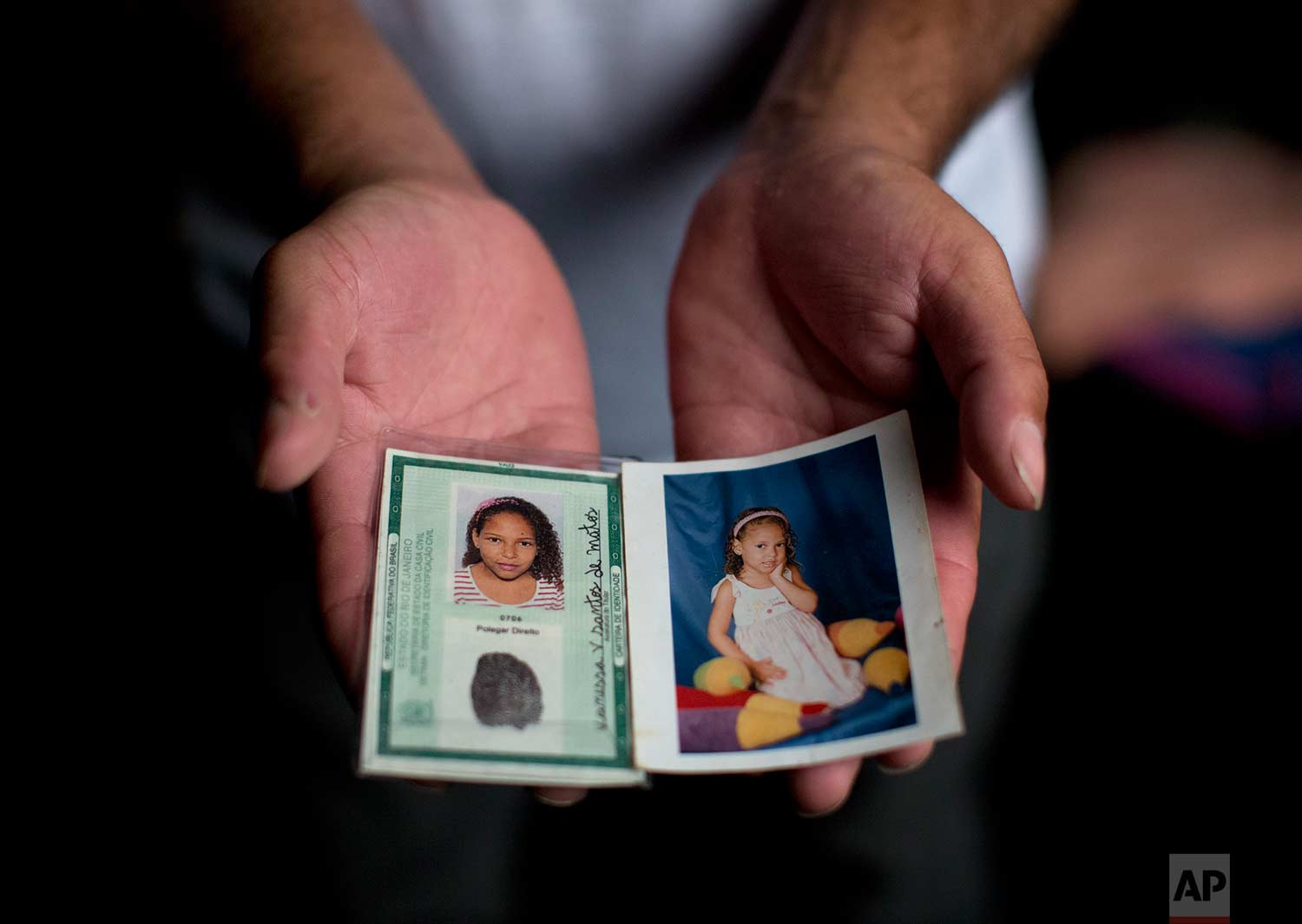 "In this July 25, 2017 photo, Leandro Monteiro de Matos holds a photo and school identification of his slain daughter Vanessa, in Rio de Janeiro, Brazil. On July 4, a group of police officers on patrol barged into the home of 10-year-old Vanessa dos Santos in the ""pacified"" Lins complex of slums. Allegedly they were searching for a suspect, but only the girl was inside. (AP Photo/Silvia Izquierdo)"