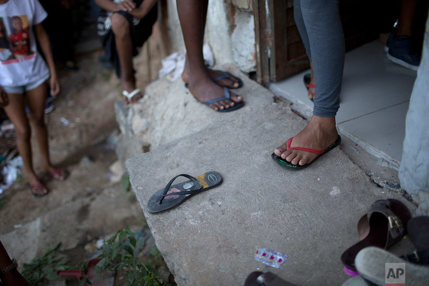 In this July 6, 2017 photo, youths stand on the doorstep where 10-year-old Vanessa dos Santos fell dead, in the Lins complex of slums, in Rio de Janeiro, Brazil. When police officers on patrol barged into the home, Vanessa's godmother and neighbor shouted for her to leave the house immediately. As Vanessa leaned down to pick up her flip-flops, shooting erupted. She died on the doorstep from a high caliber bullet wound to the head. (AP Photo/Silvia Izquierdo)