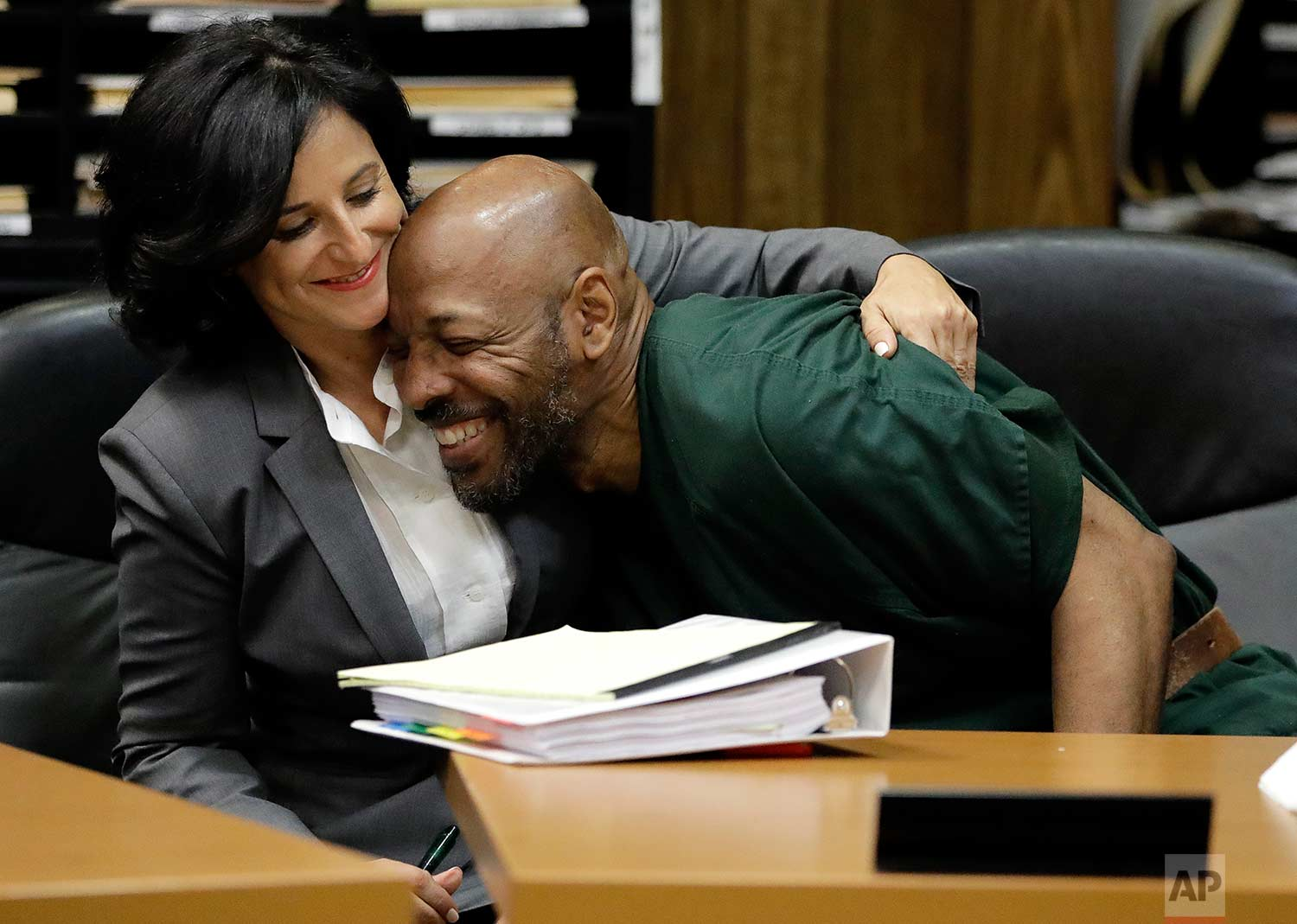 Eric Kelley, right, is hugged by his lawyer Vanessa Potkin moments after Passaic County Superior Court Judge Joseph Portelli granted Kelley a retrial in the case in which he was found guilty of the killing of a video store employee during a robbery in 1993, during a hearing, Friday, Sept. 15, 2017, in Paterson, N.J. Kelley and Ralph Lee, who was not present during the hearing, had been convicted and were currently serving terms. The new trials were granted after new DNA tests linked an important piece of evidence to another man. (AP Photo/Julio Cortez)