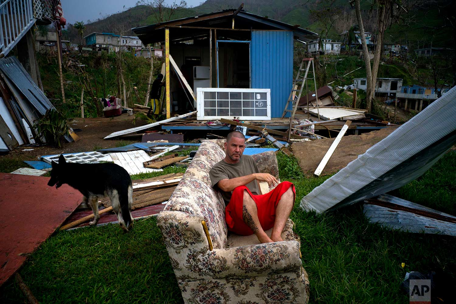 In this Saturday, Sept. 30, 2017 photo, Angel Rodriguez poses next to his belongings in front of his house, destroyed by Hurricane Maria, in the San Lorenzo neighborhood of Morovis, Puerto Rico. (AP Photo/Ramon Espinosa)