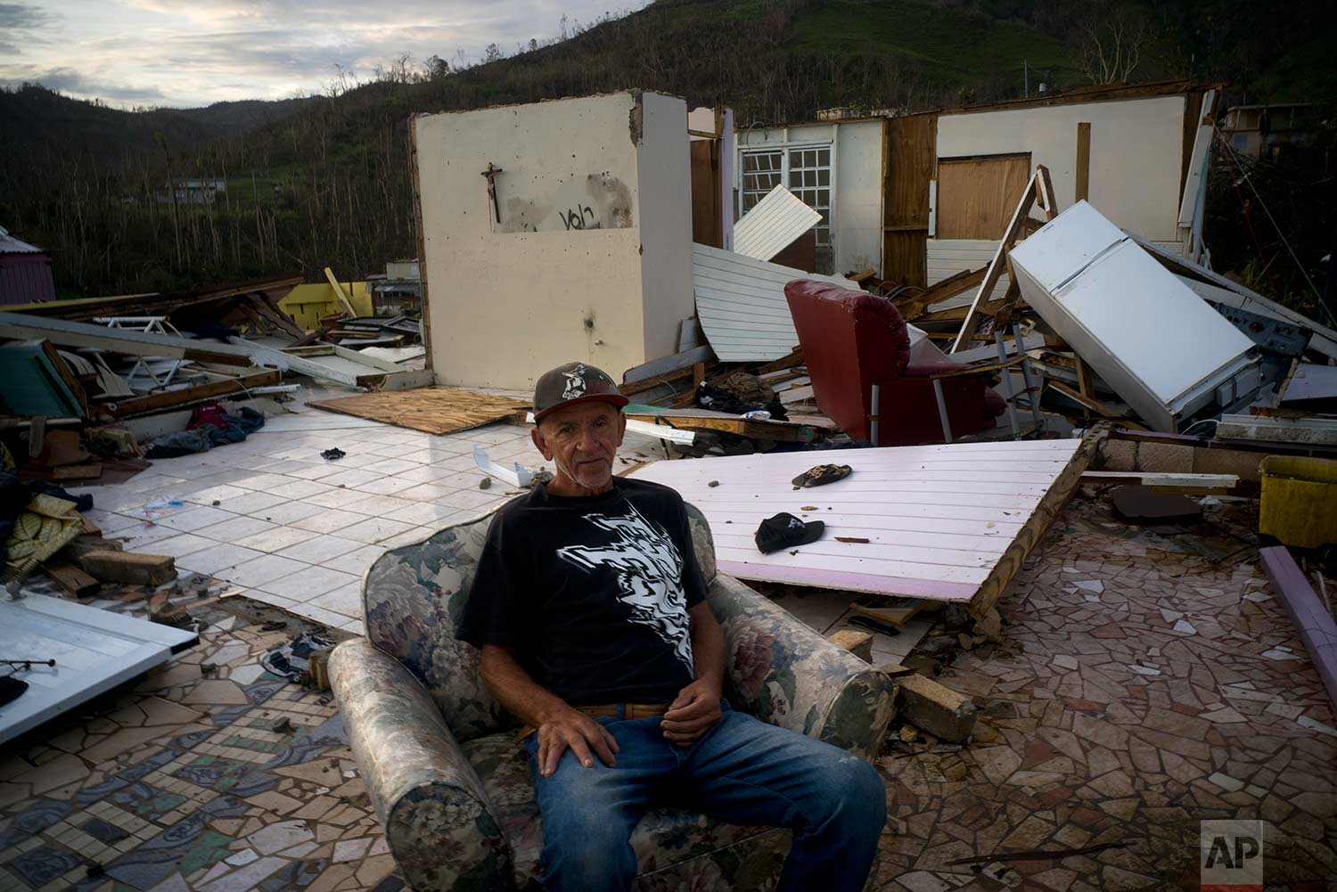 Luis Cosme poses sitting in an armchair in what is left of his house destroyed by Hurricane Maria, in Morovis, Puerto Rico, Sunday, Oct. 1, 2017. (AP Photo/Ramon Espinosa)