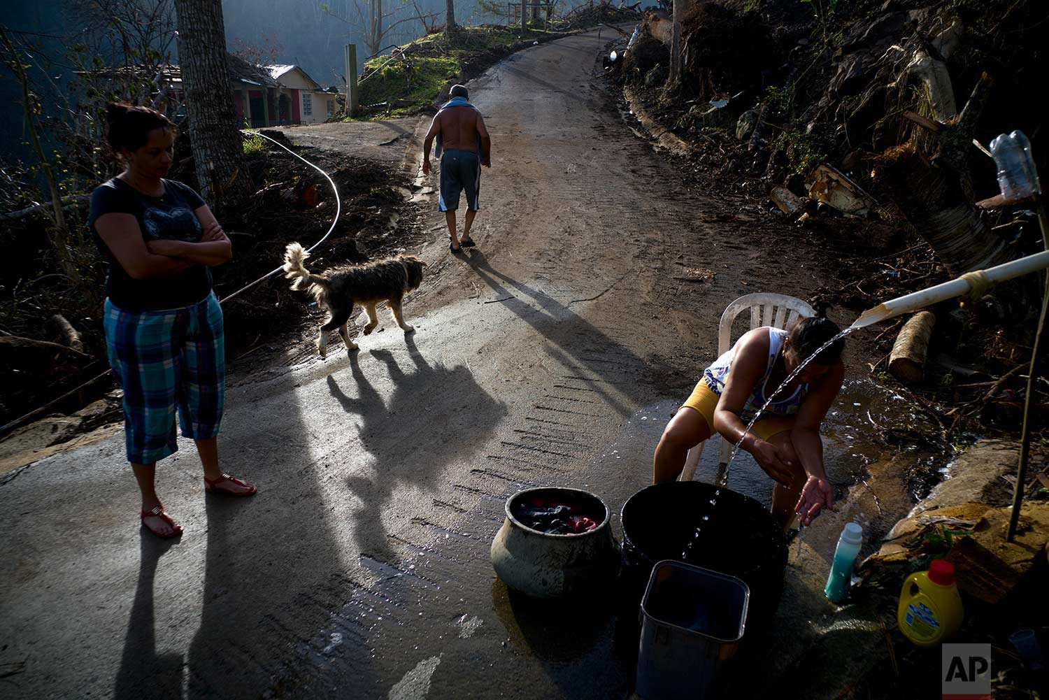 A woman washes her clothes with water from the mountain while Ramon Sortre Vazquez walks with his dog, in Morovis, Puerto Rico, Sunday, Oct. 1, 2017. (AP Photo/Ramon Espinosa)