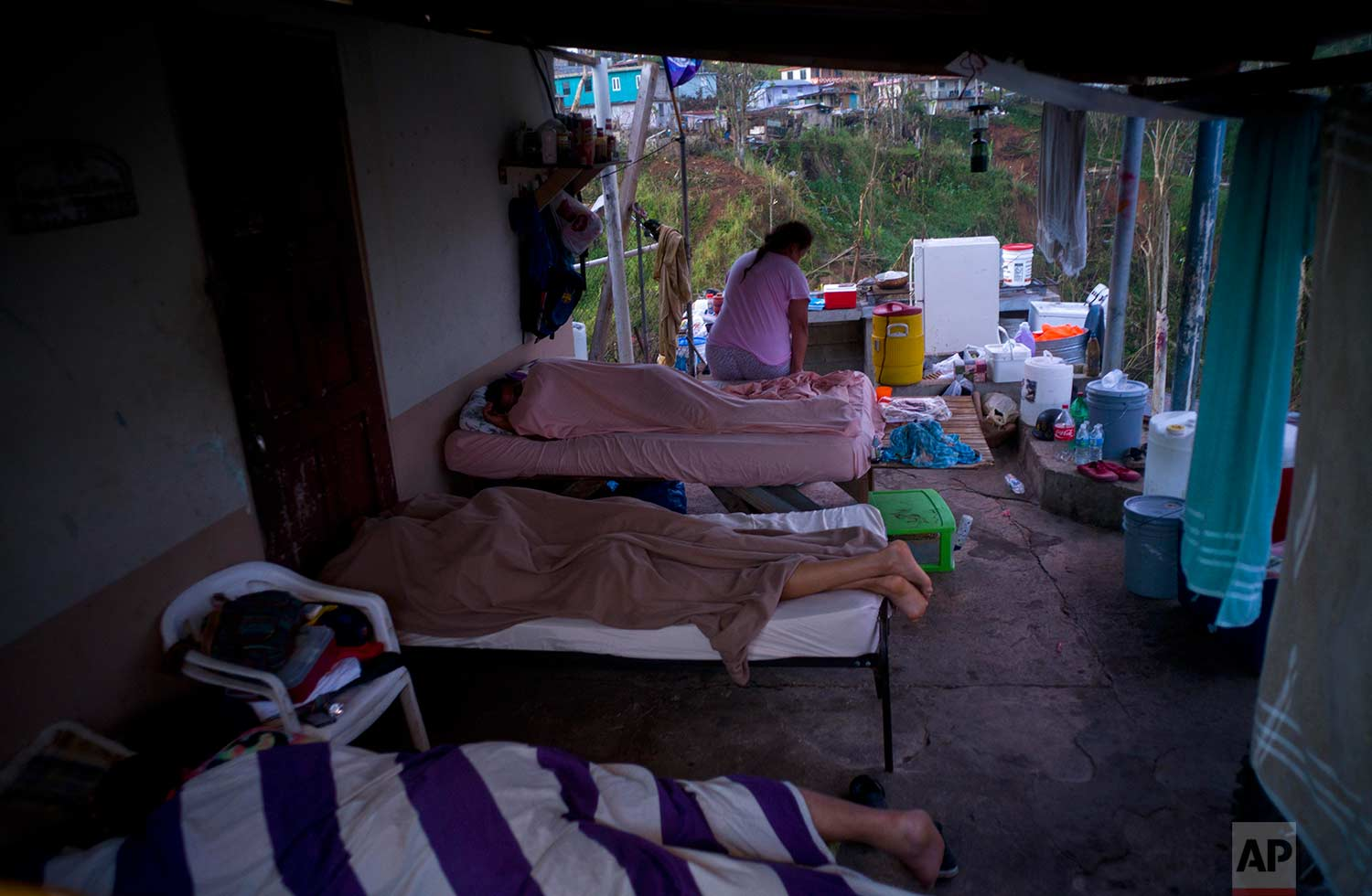 Julia Rivera gets up from the makeshift bed in the porch of her house as her children sleep, in Morovis, Puerto Rico, Sunday, Oct. 1, 2017. (AP Photo/Ramon Espinosa)