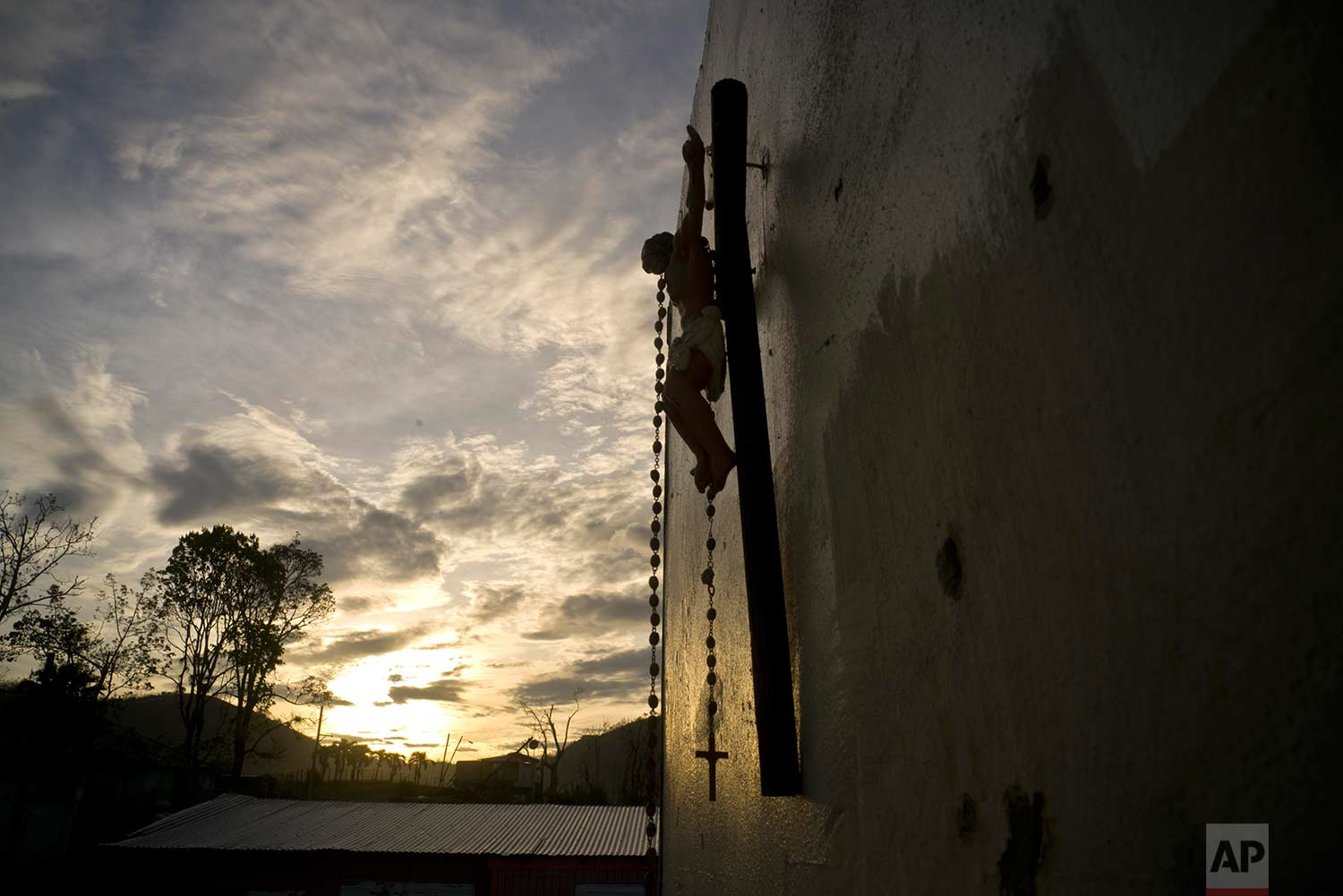 A cross hangs from a wall that remains of Luis Cosme's house, destroyed by Hurricane Maria, in the San Lorenzo neighborhood of Morovis, Puerto Rico, Sunday, Oct. 1, 2017. (AP Photo/Ramon Espinosa)