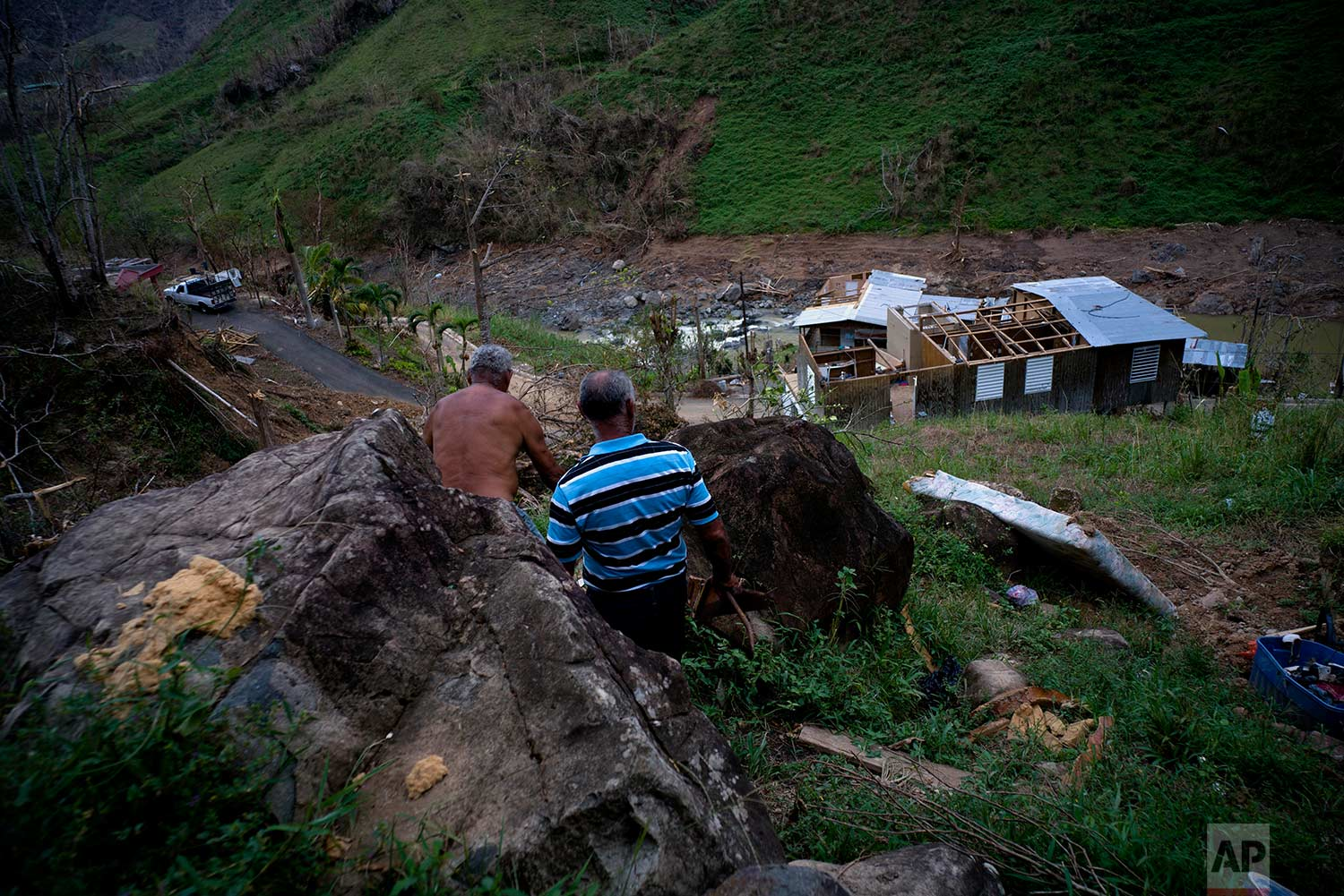 Salvador Sortre Vazquez , center, and his brother Angel Luis walk on the mountain in the direction of what is left of their house destroyed by Hurricane Maria, in Morovis, Puerto Rico, Sunday, Oct. 1, 2017. (AP Photo / Ramon Espinosa)