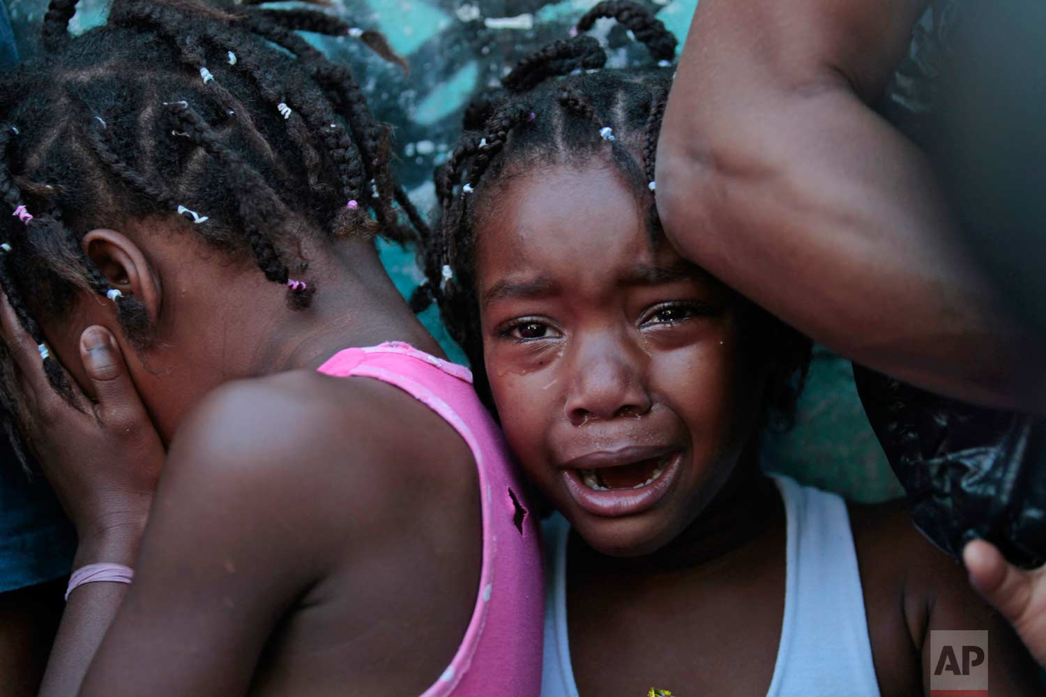In this Nov. 27, 2010 photo, children cry during a shootout between police and drug traffickers in the Alemao complex of slums, in Rio de Janeiro, Brazil. Soldiers and police crouched behind armored vehicles trained their rifles on dozens of entrances to the complex where more than 85,000 people live, giving drug traffickers a chance to surrender before they stormed what is considered the most dangerous area of Rio. (AP Photo/ Silvia Izquierdo)