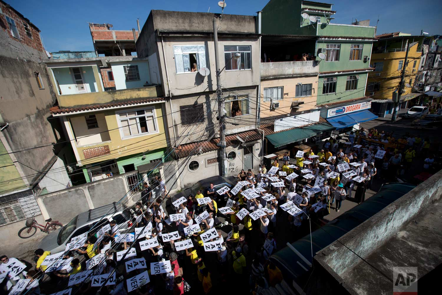 In this May 24, 2017 photo, residents and activists march demanding an end to the gun battles between police and gangs that put residents in the crossfire, in the Mare complex of slums, in Rio de Janeiro, Brazil. With an average of 15 shootings a day, gunfire is often heard across the city that hosted the Summer Olympic Games just a year ago. (AP Photo/Silvia Izquierdo)