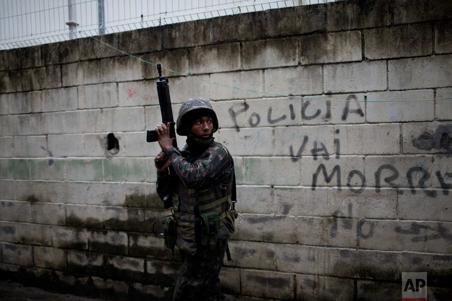"""In this Aug. 21, 2017 photo, a soldier takes position during a security operation next to a wall spray painted with a message that reads in Portuguese: """"Police die,"""" in the Jacarezinho slum, in Rio de Janeiro, Brazil. Thousands of soldiers and police are occupying a series of slum communities in northern part of the city as part of efforts to combat a spike in violence. (AP Photo/Silvia Izquierdo)"""
